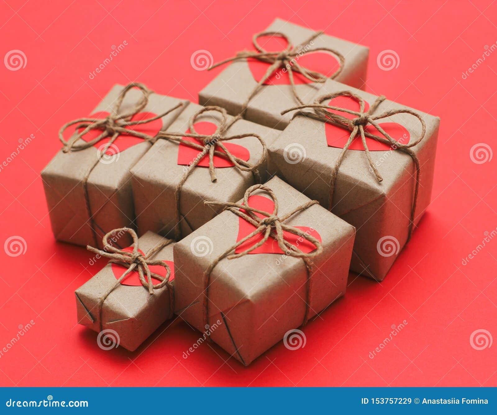 Metta dei contenitori di regalo marroni Avvolto in carta del mestiere e legato dal cavo della canapa Carta decorativa rossa lumin