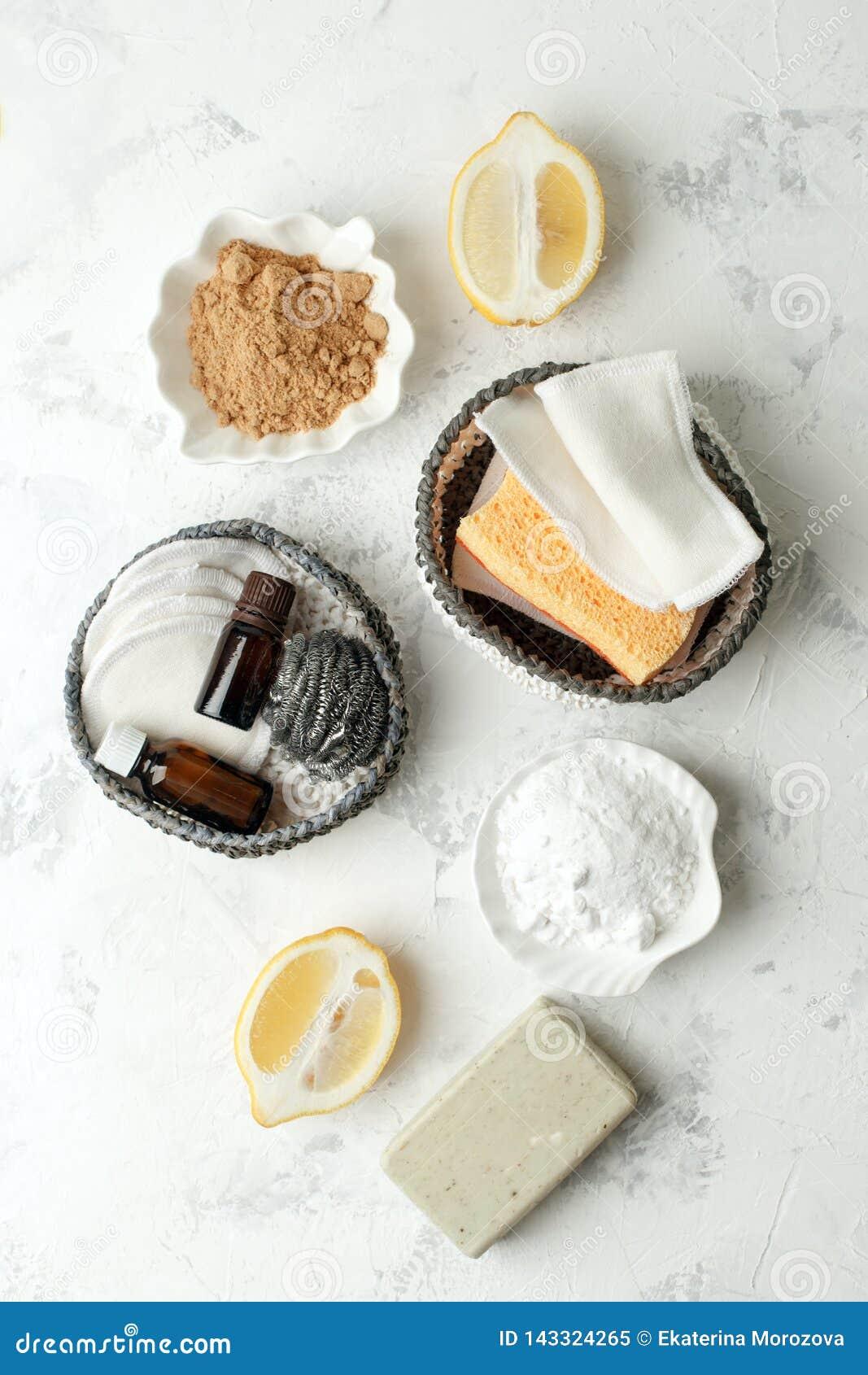 Metta dei prodotti di pulizia naturali ecologici sul tavolo da cucina di legno: senape, soda, oli essenziali, spugna di cellulosa