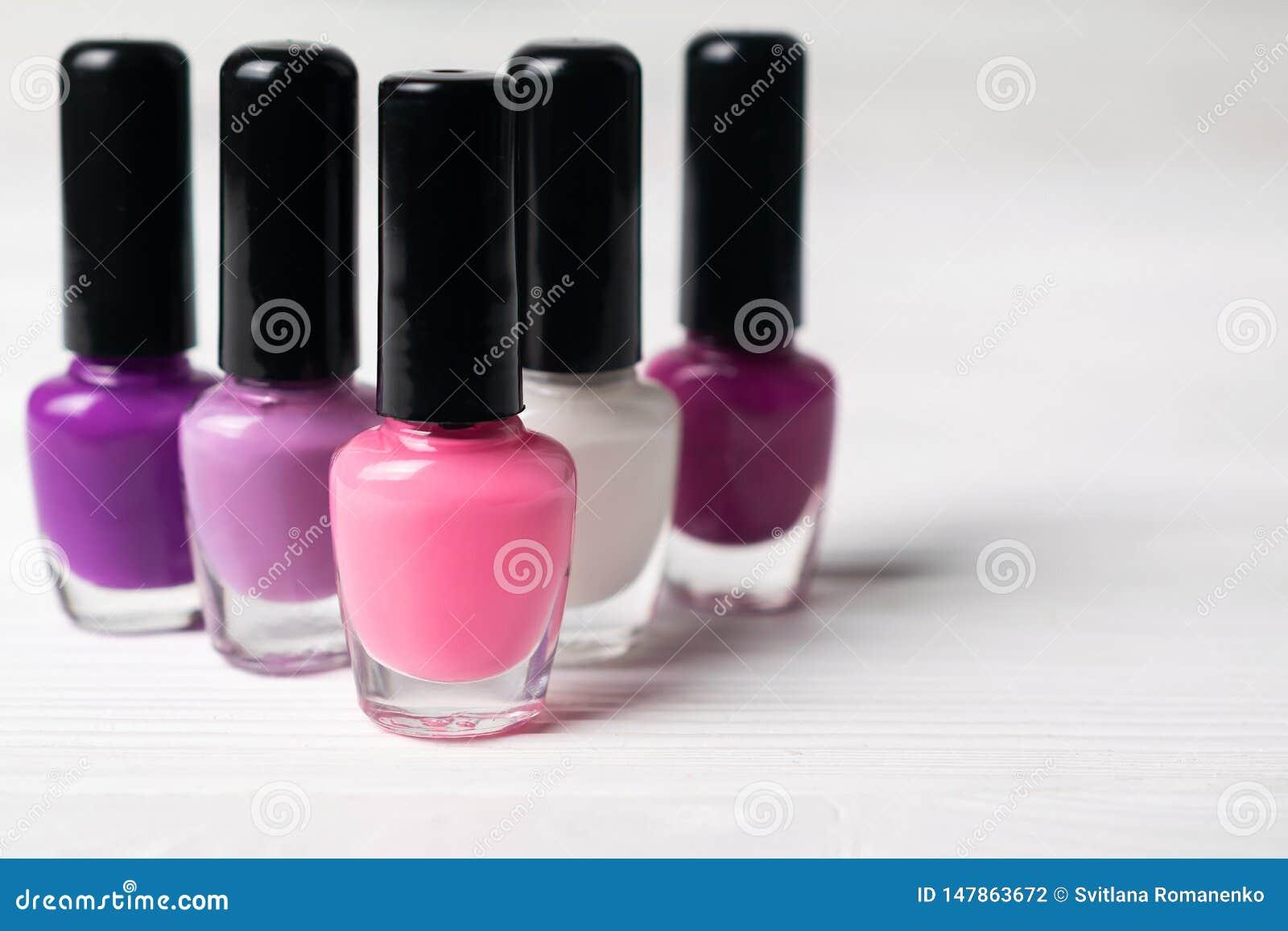 Metta delle bottiglie variopinte viola e di rosa dello smalto