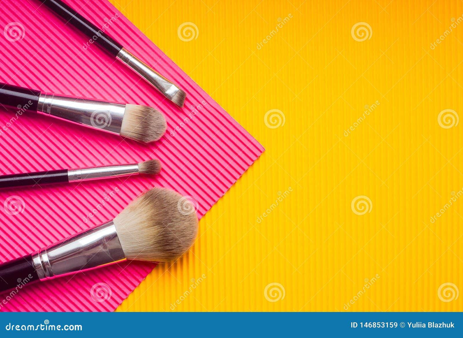 Metta delle spazzole di trucco contro fondo multicolore Punto di vista superiore, disposizione piana