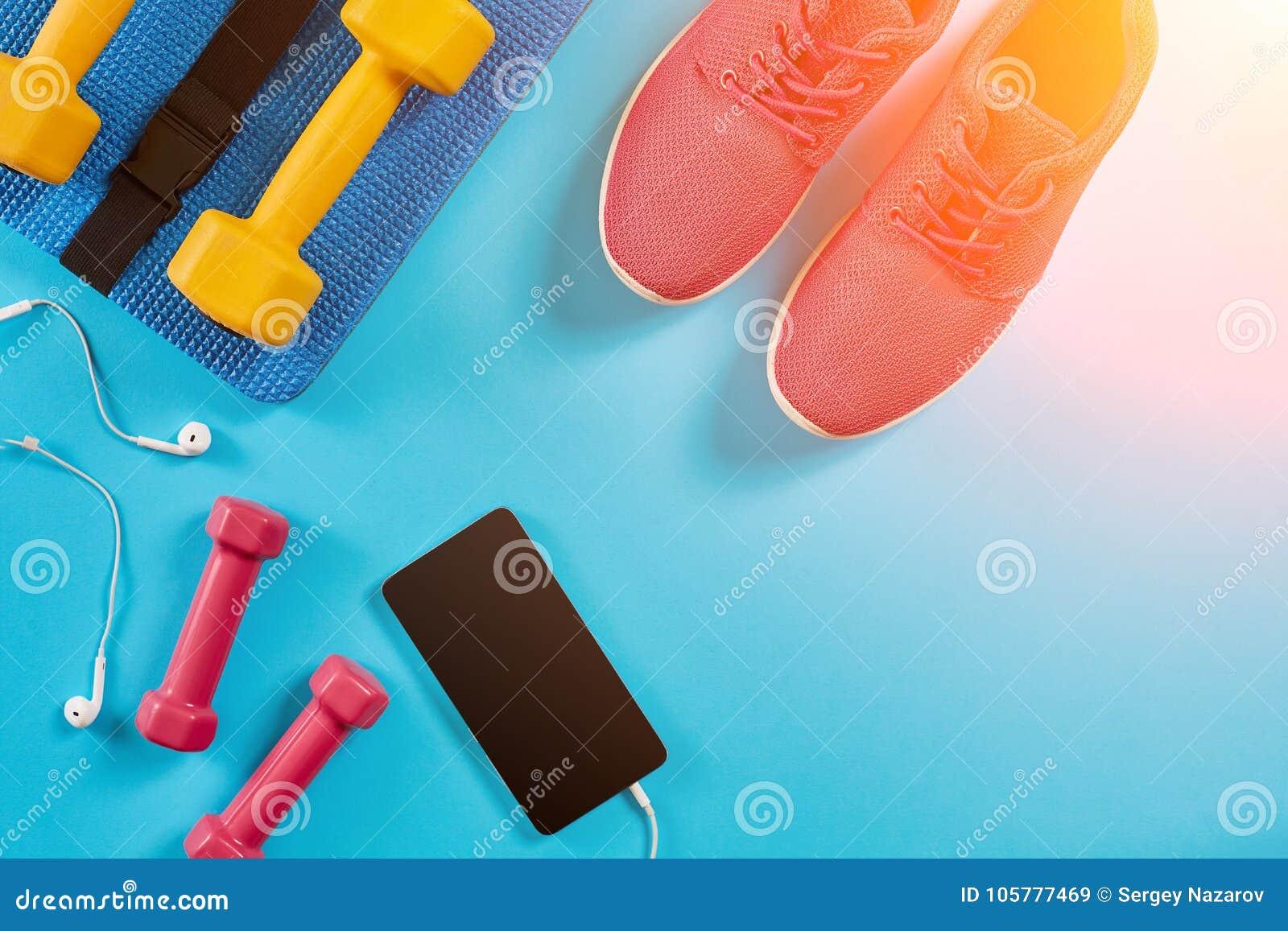 Metta in mostra le scarpe, le teste di legno ed il telefono cellulare su fondo blu Vista superiore Forma fisica, sport e concetto