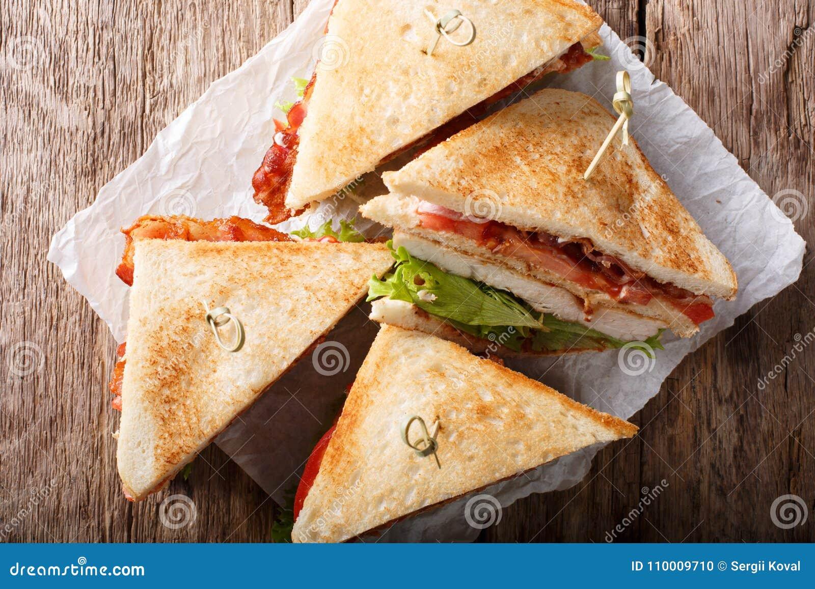 Metta a strati il panino di club con carne di tacchino, bacon, i pomodori e il lettuc
