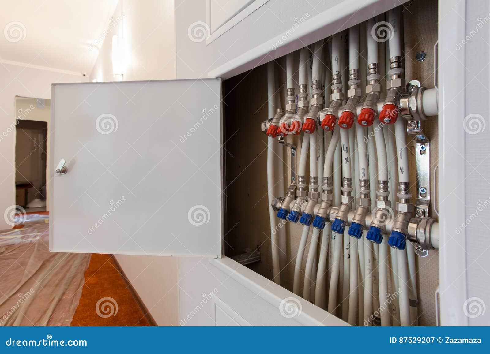 Mettant d aplomb les tuyaux en plastique blancs, des garnitures et les robinets à tournant sphérique sont installés en appartemen