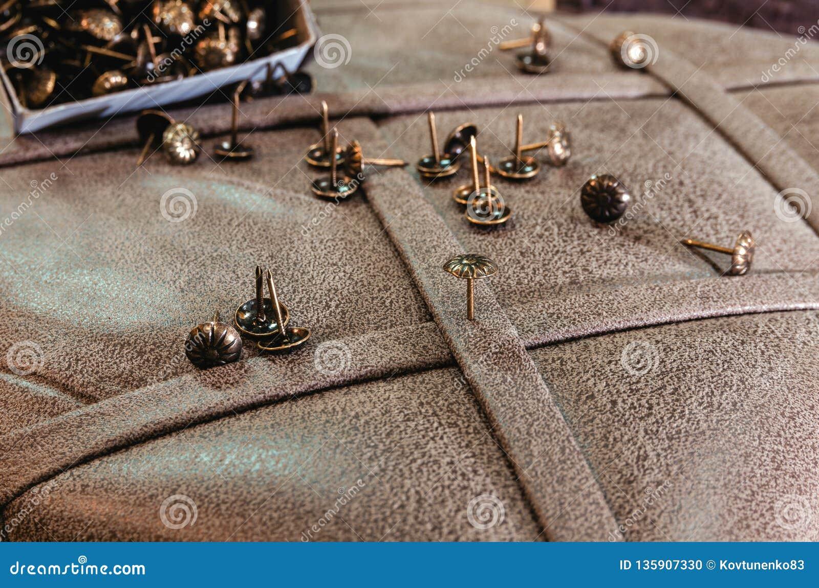 Meubilair decoratieve spijkers op de achtergrond van stoffenstoffering