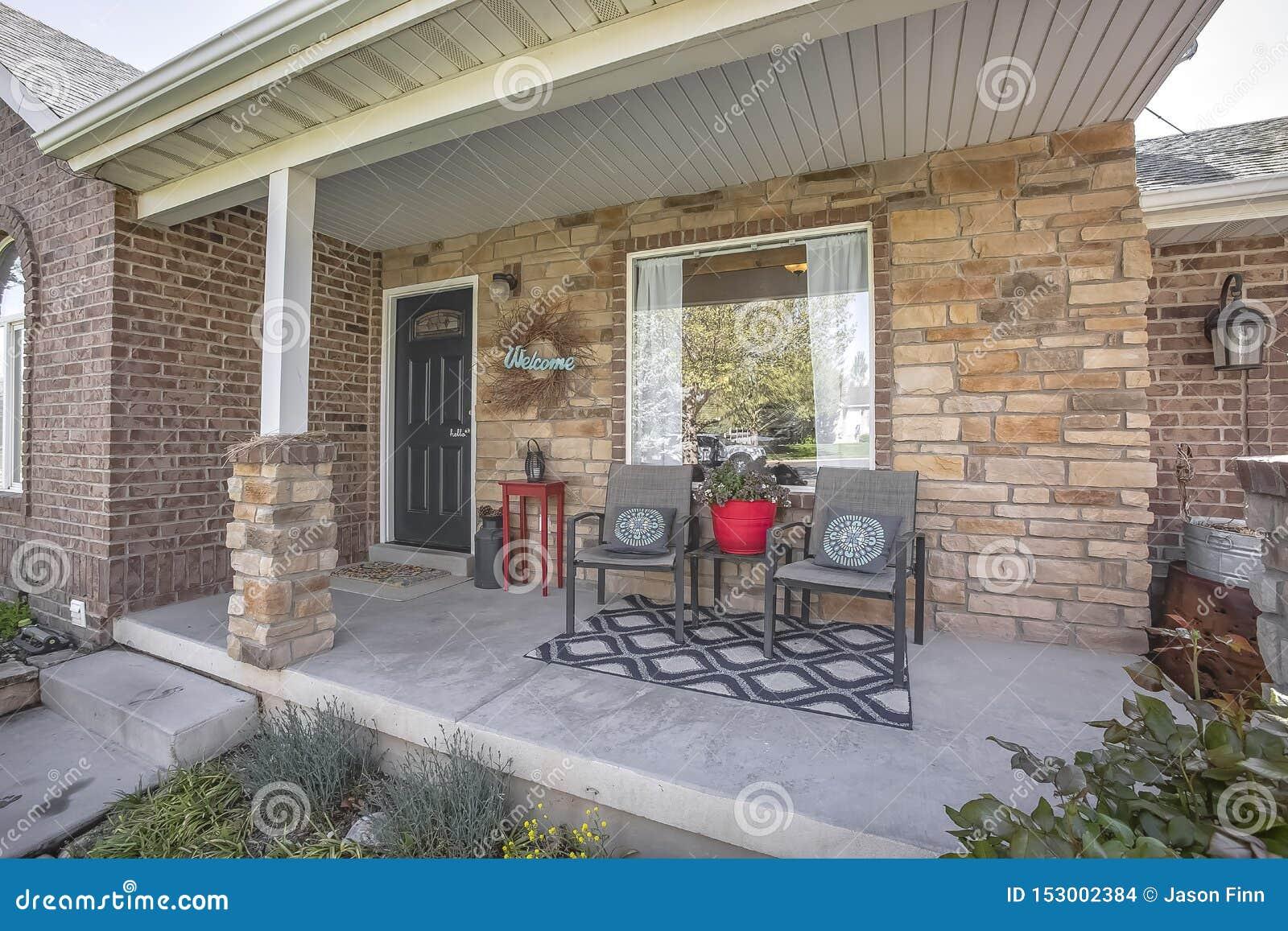Meubilair en Welkome kroon op de portiek van huis met rode baksteen buitenmuur