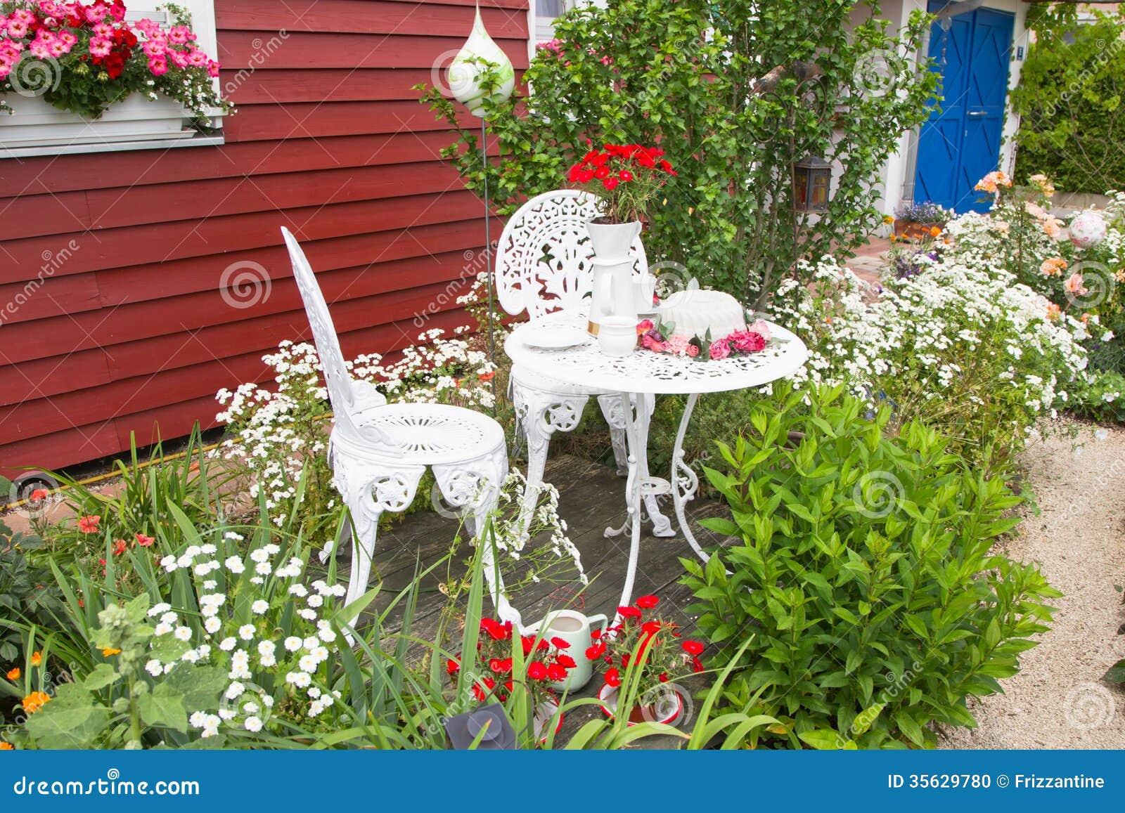 Meubles de jardin r gl s avec des fleurs devant la maison for Ameublement de jardin