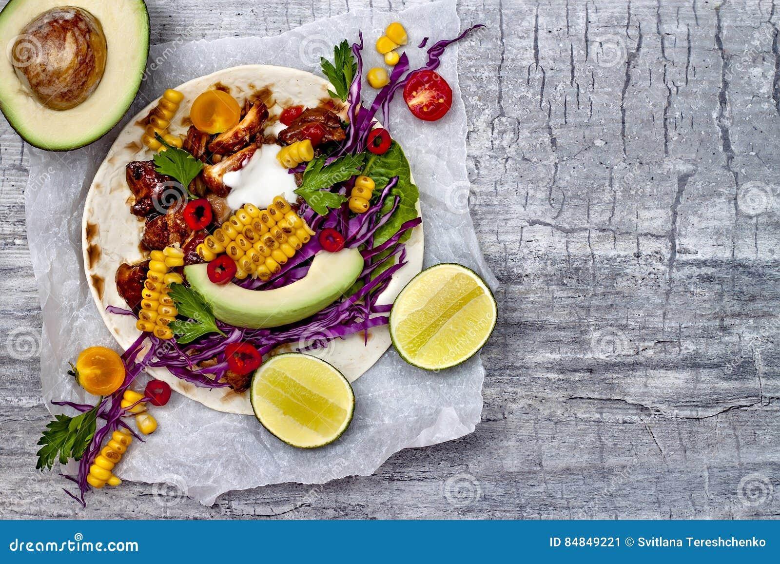 Mexicaanse taco s met avocado, langzaam gekookt vlees, geroosterd graan, rode kool slaw en Spaanse pepersalsa op rustieke steenli