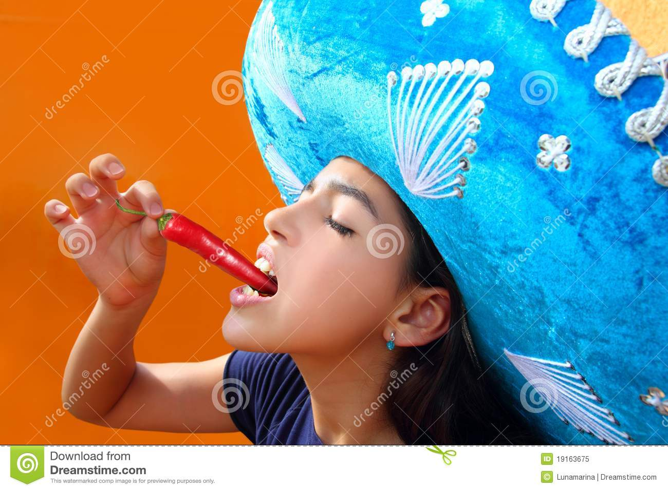 mexican girl eating red hot chili pepper stock image - image of