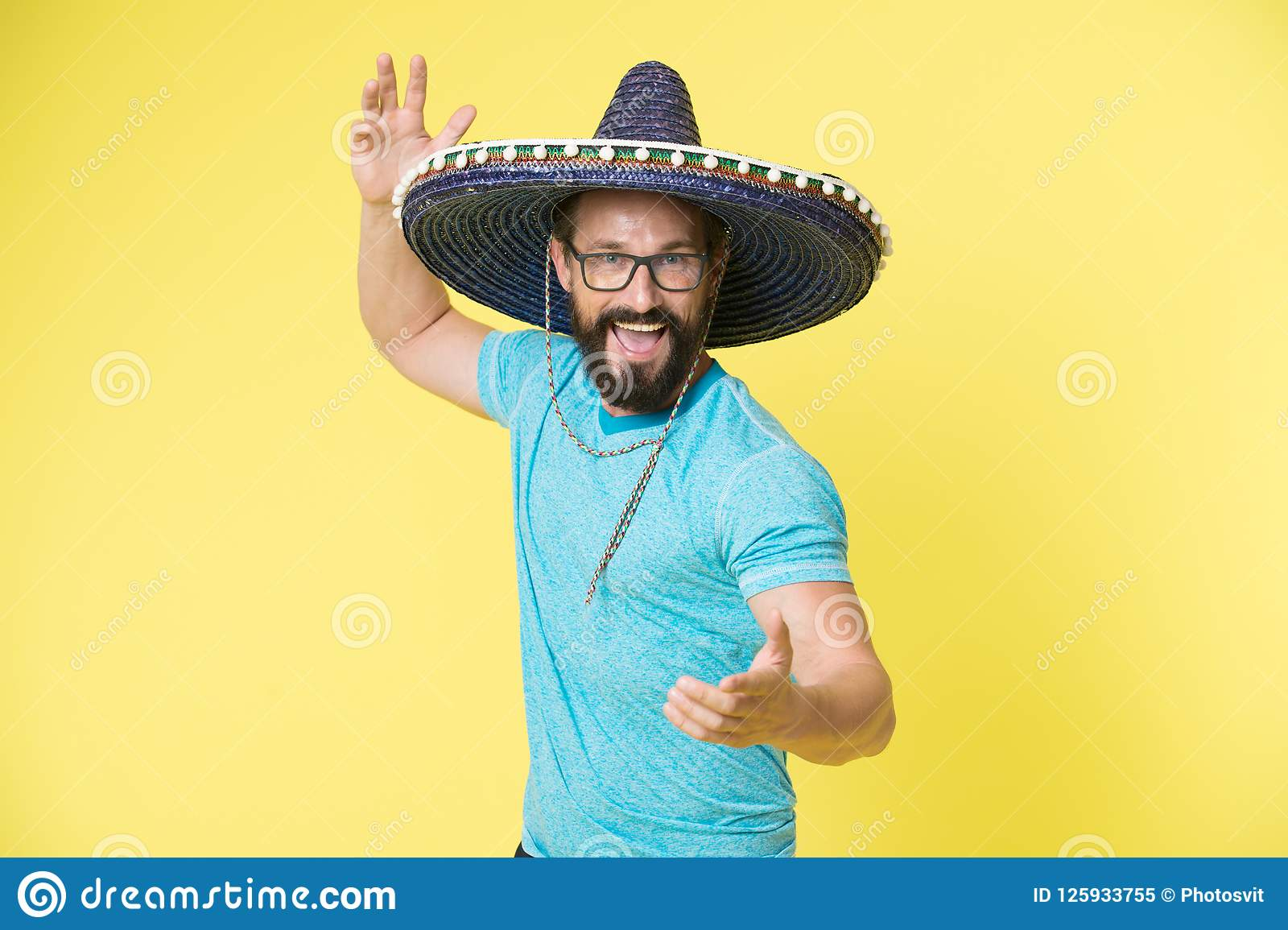 Mexican party concept. Man cheerful happy face in sombrero hat celebrating yellow background. Guy with beard looks
