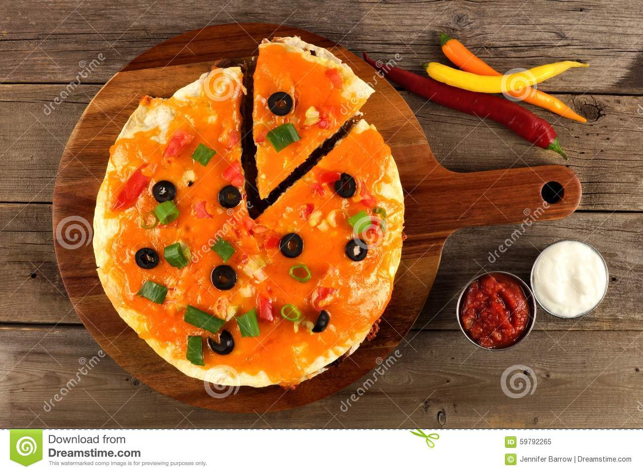 Mexican pizza with cut slice on wood server, downward view