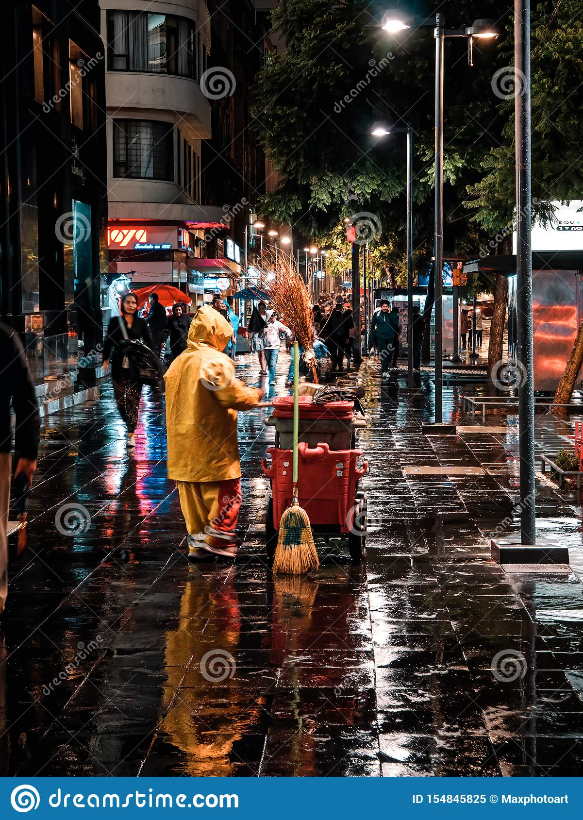 Woman sweeper cleans the sidewalk at night in Mexico City