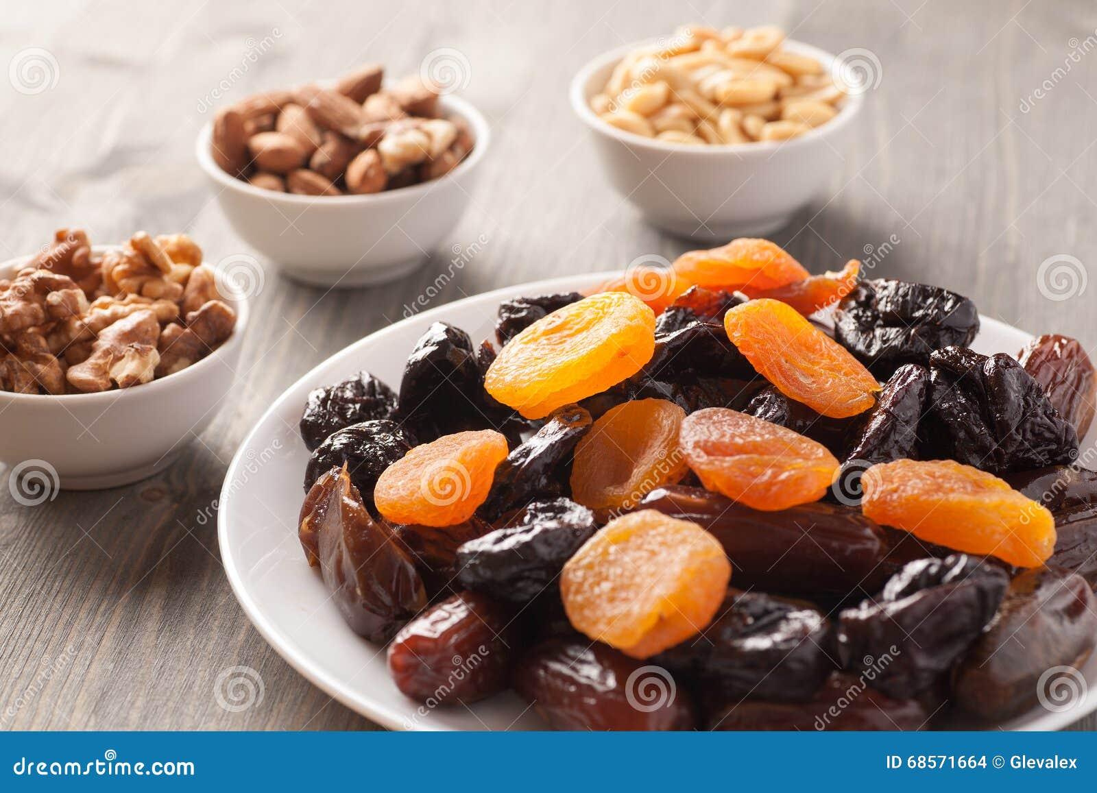 Mezcla de frutas y de nueces secadas en una tabla de madera