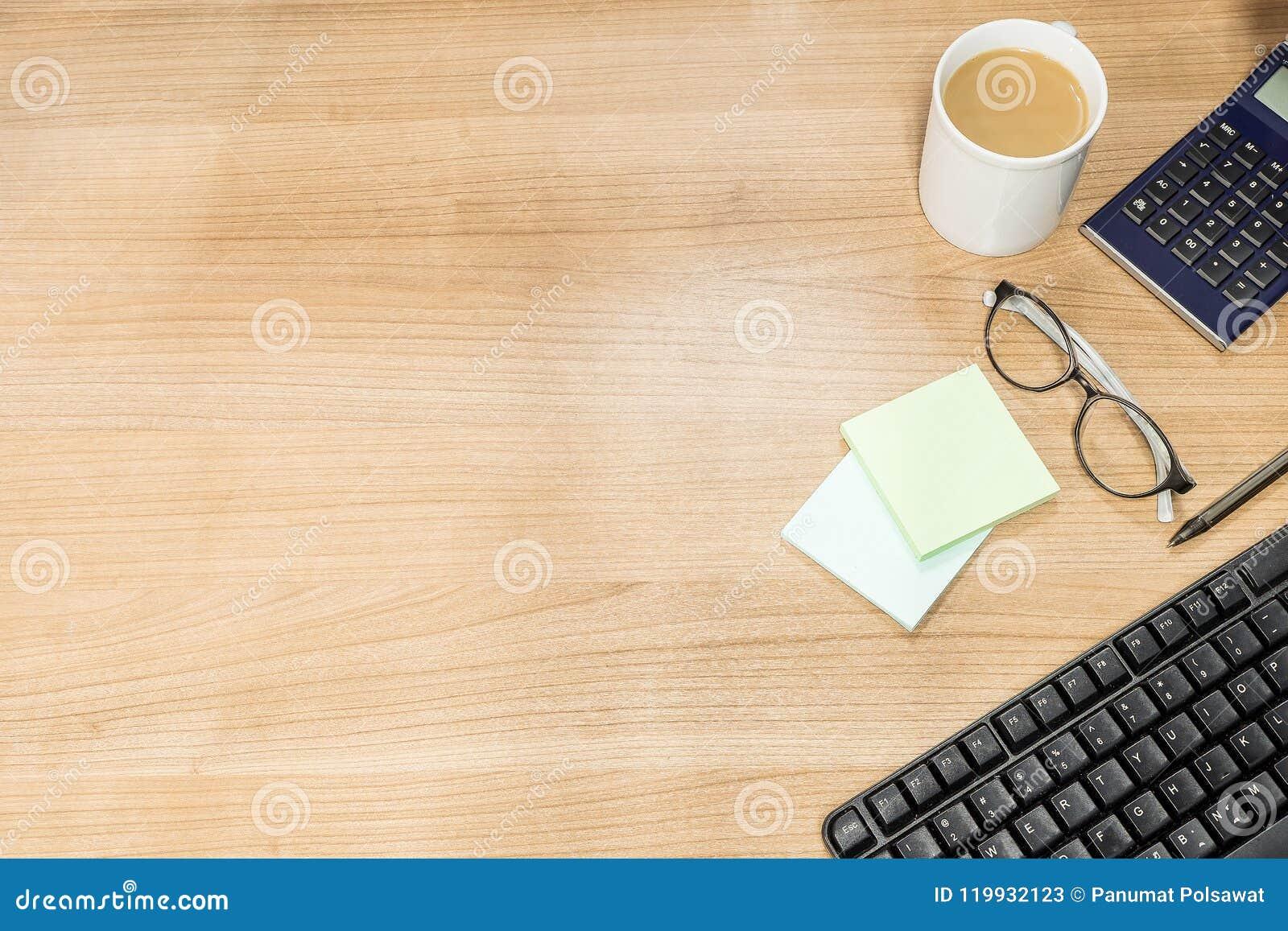 Mezcla de materiales de oficina y de artilugios en un fondo de madera de la tabla