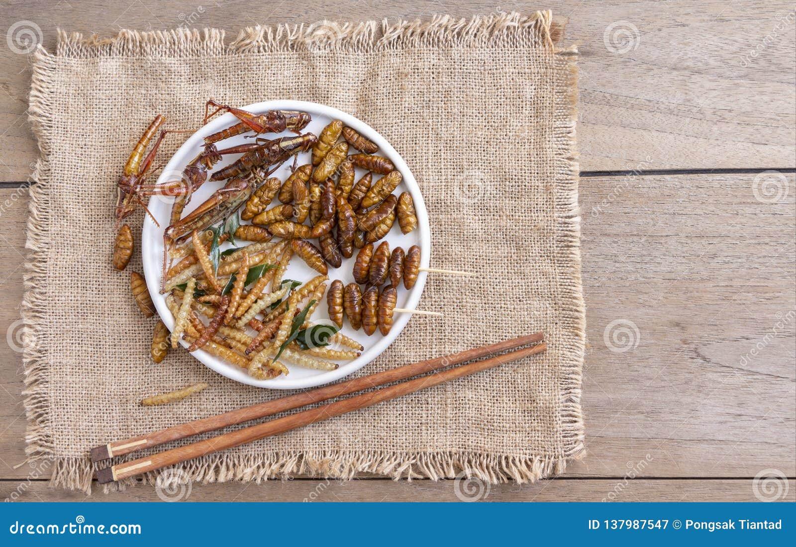 Mezclado de gusano y de insectos curruscantes en una placa de cerámica con los palillos en una tabla de madera El concepto de fue