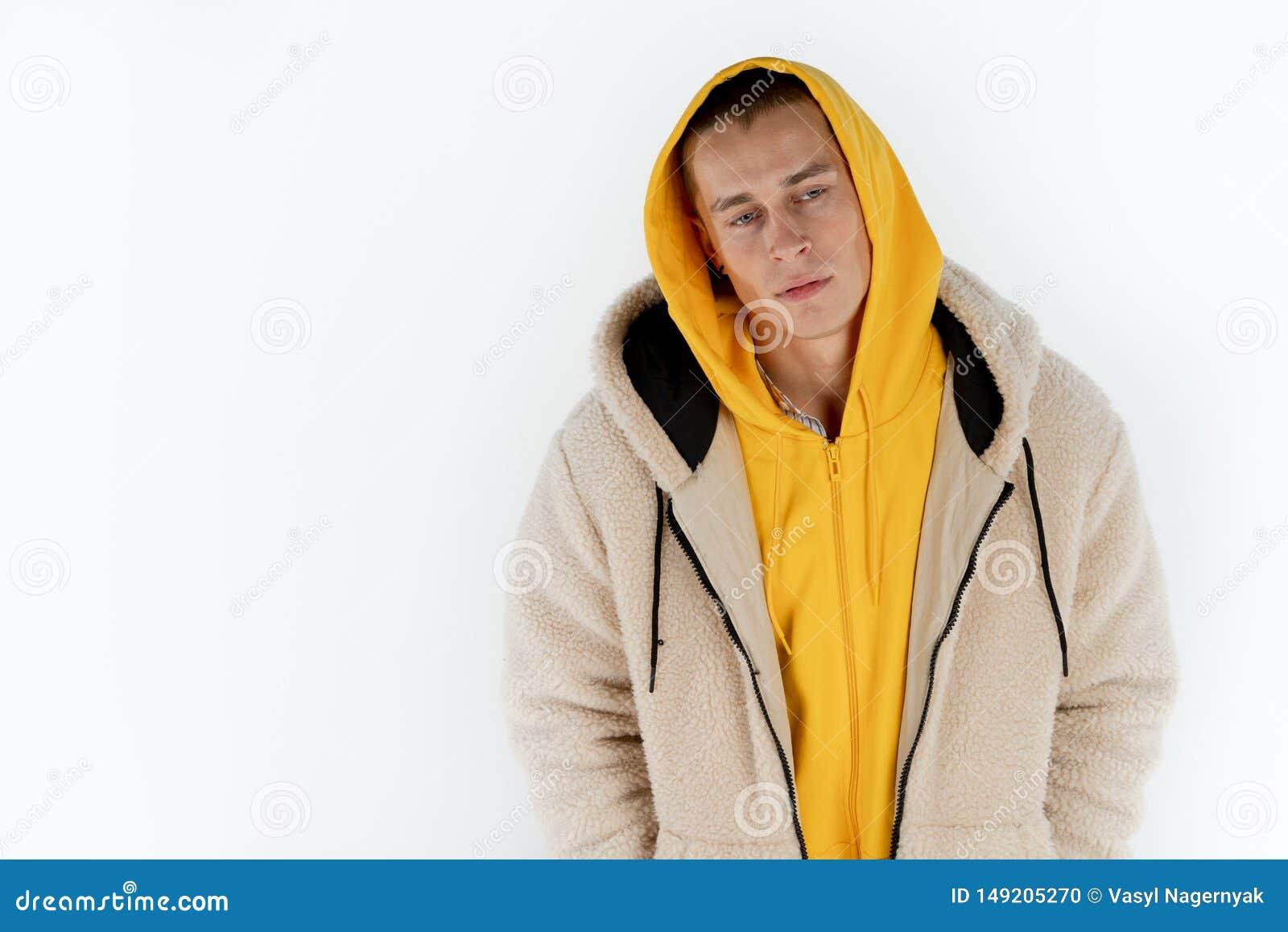 Mezzo ritratto di lunghezza di giovane uomo infelice turbato che indossa condizione gialla di maglia con cappuccio contro il fond