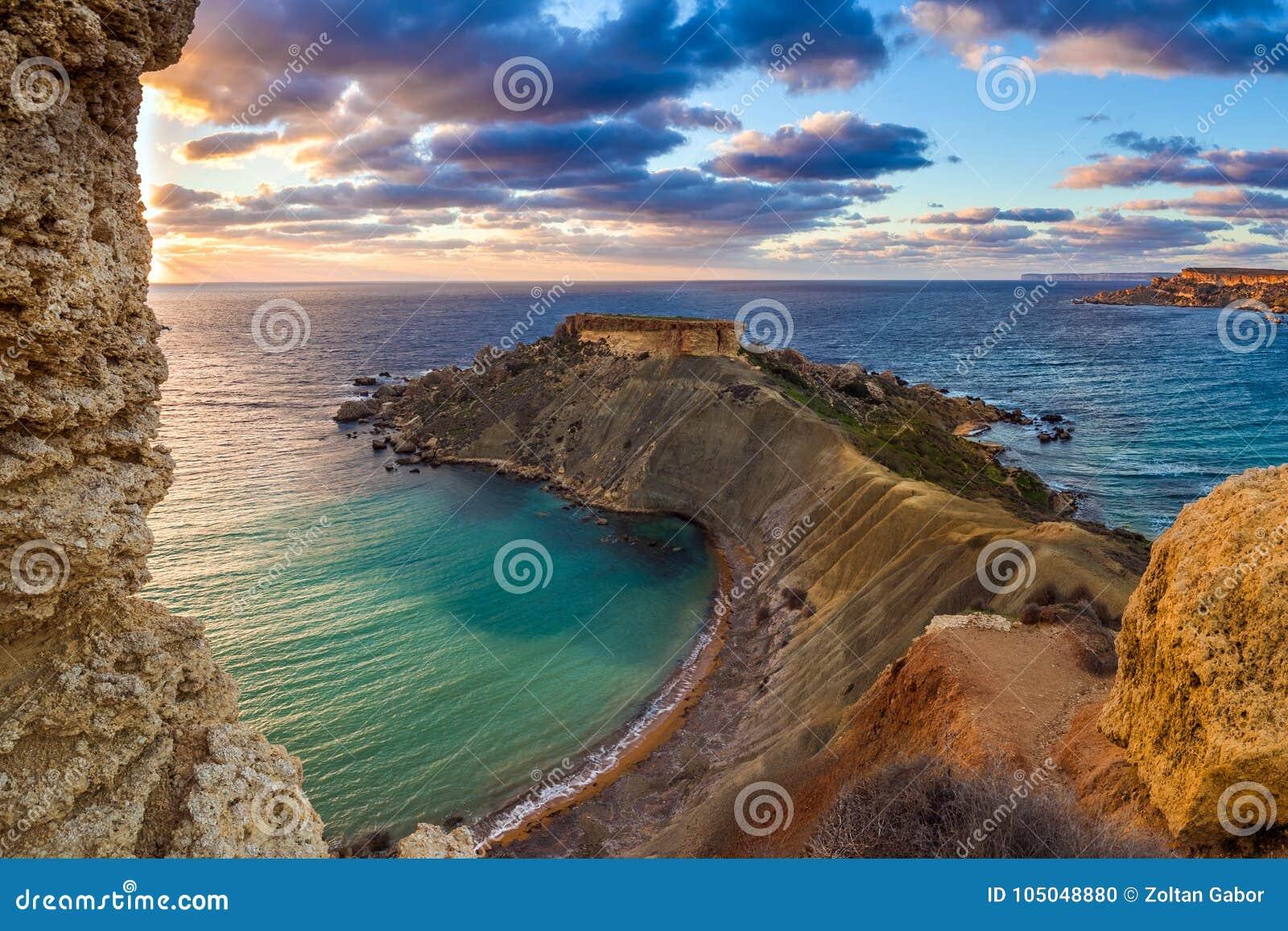 Mgarr Malta - panorama av Gnejna och Ghajn Tuffieha skäller, den mest härliga stranden två i Malta på solnedgången
