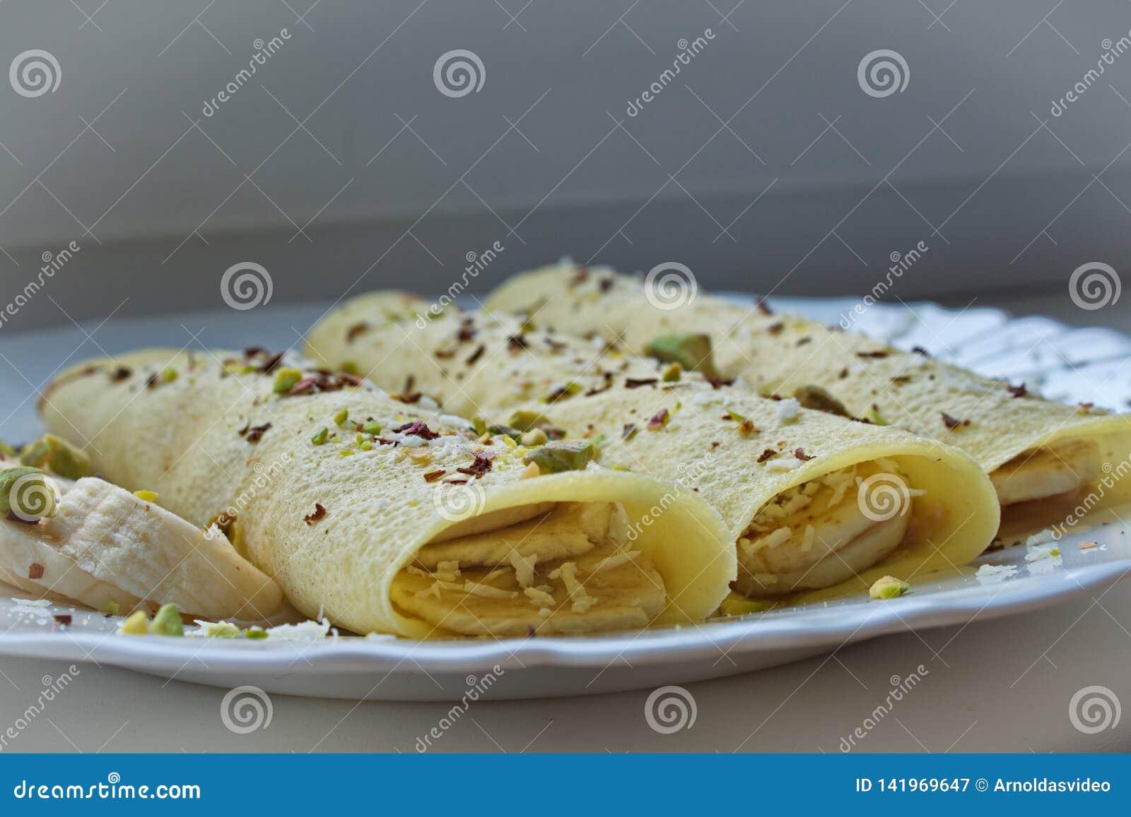 Miękka ostrość zamknięta w górę 3 krepa blinów z masłem orzechowym i banany nakrywający z czekoladą, cocos pistacje i golenia i