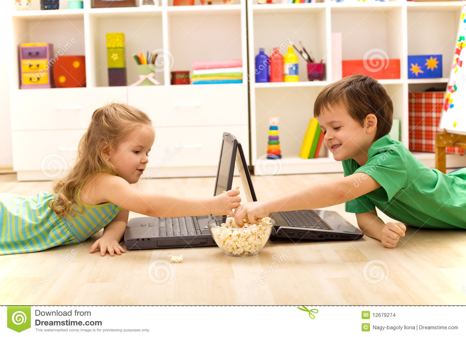 Miúdos com portáteis que comem a pipoca