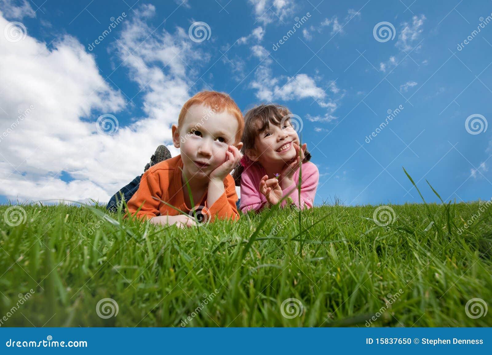 Miúdos engraçados que encontram-se na grama com céu azul