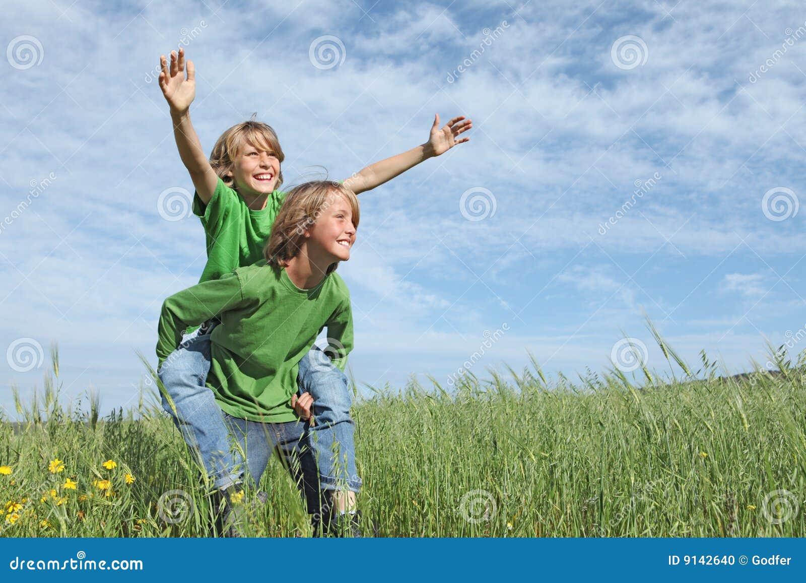 Miúdos felizes que jogam às cavalitas a raça