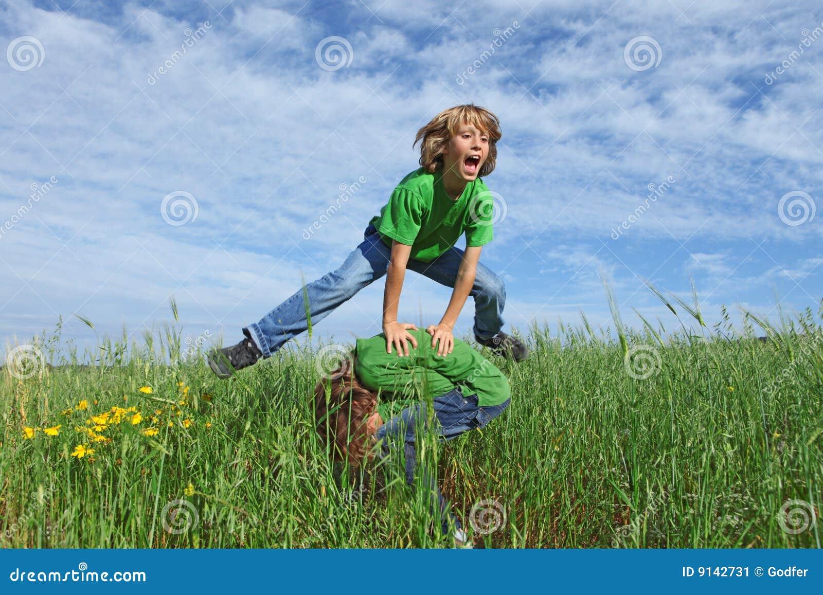 Miúdos felizes que jogam o leapfrog