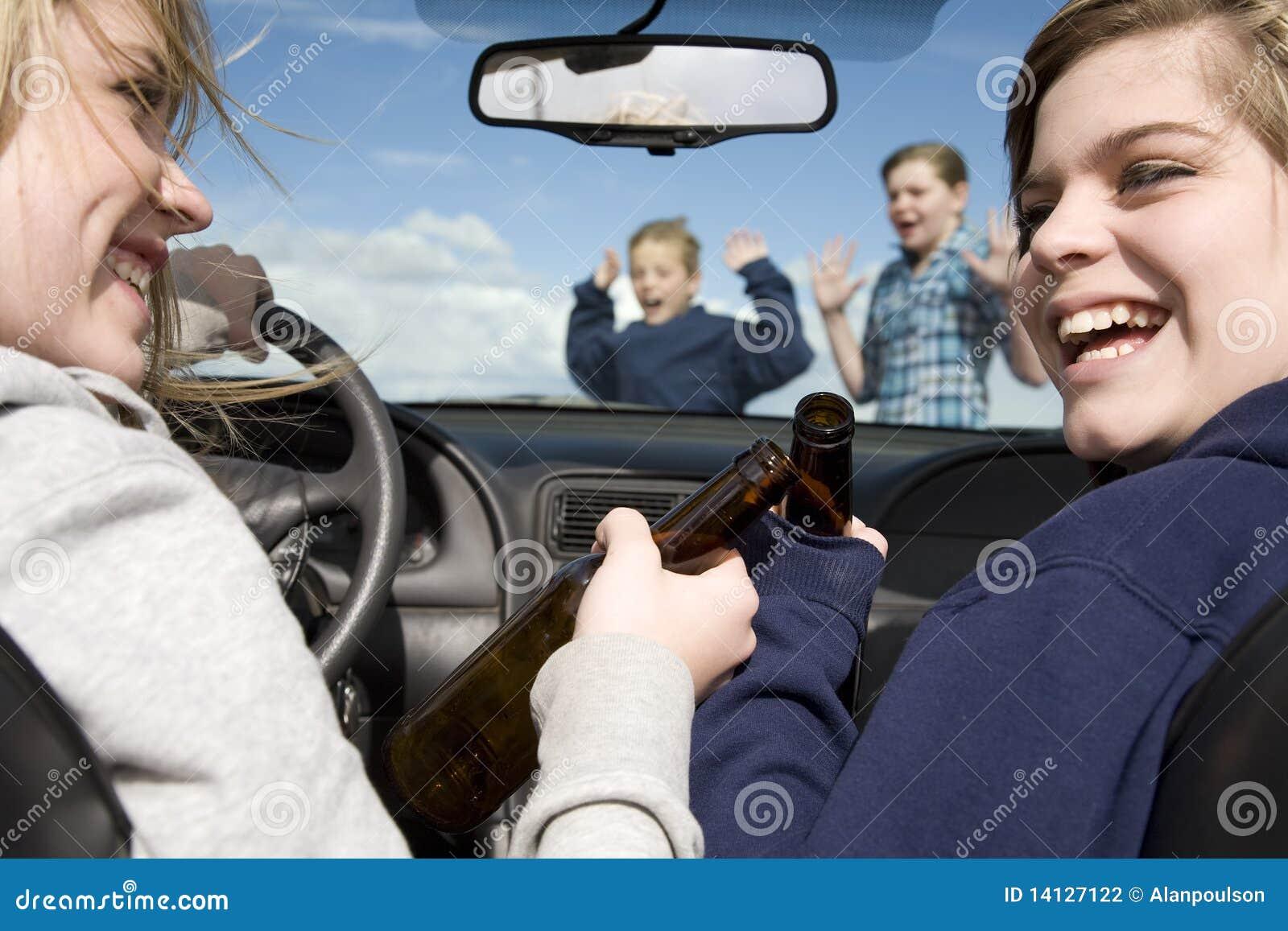 Miúdos que cruzam beber dianteiro do carro