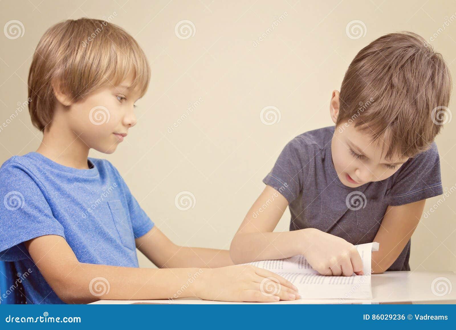 Miúdos que lêem um livro Leitura da prática do rapaz pequeno com seu irmão