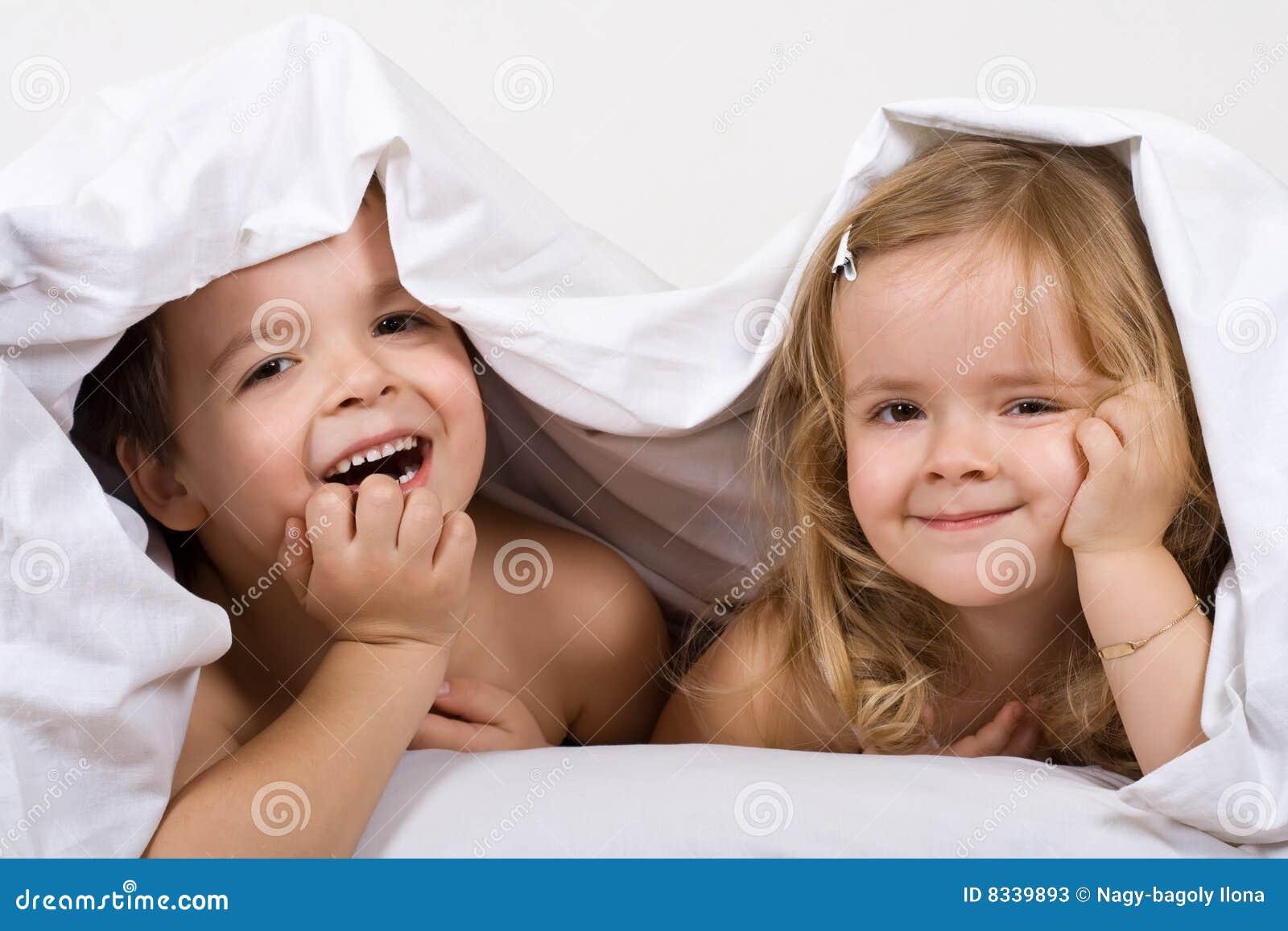Miúdos que têm o divertimento na cama