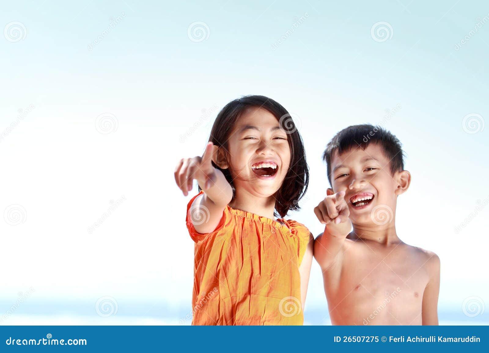 Miúdos que têm o divertimento no dia ensolarado
