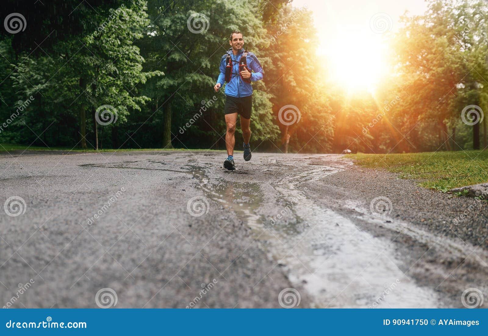 Mięśniowe łydki dysponowany męski jogger szkolenie dla przecinającego kraju lasowego śladu ścigają się w deszczu na natura śladzi