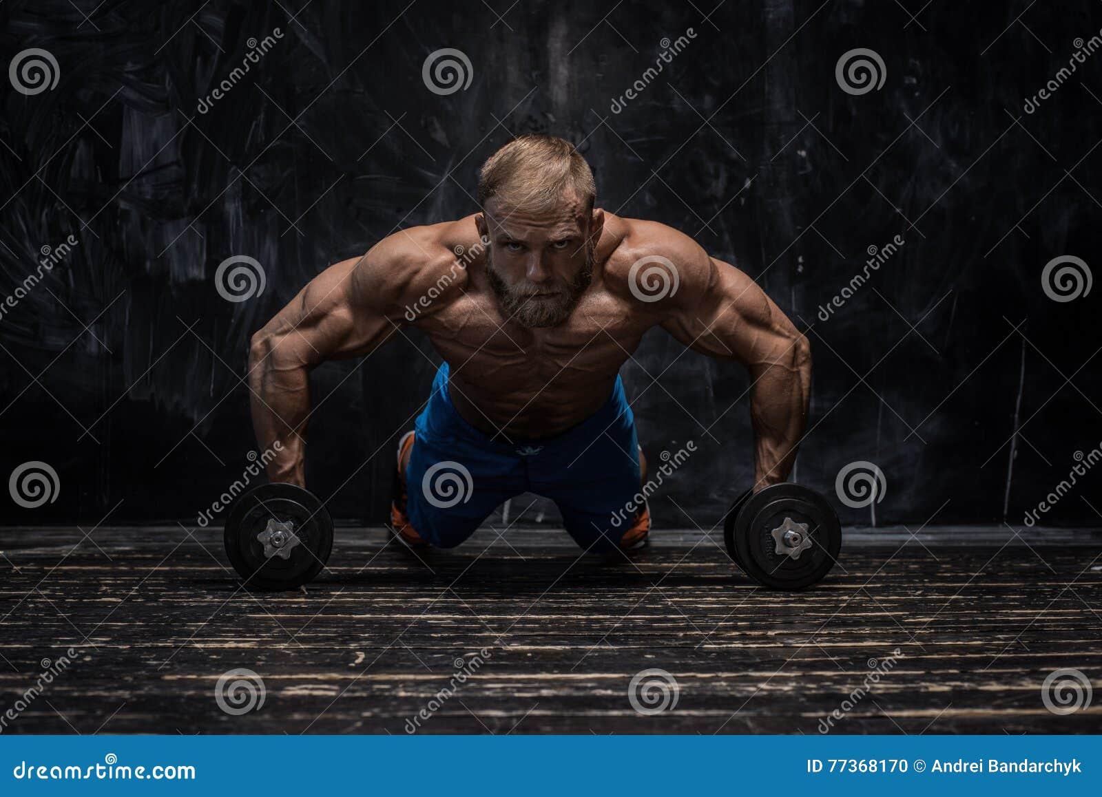 Mięśniowy bodybuilder facet nad ciemnym tłem