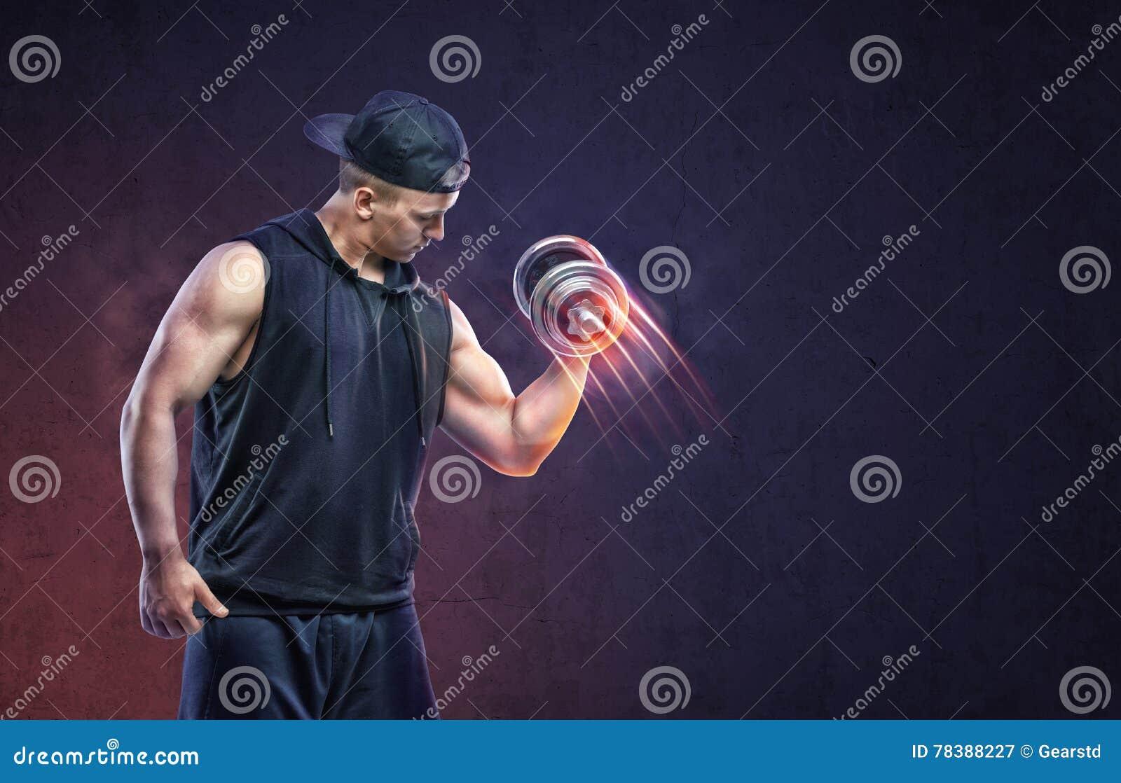 Mięśniowy młody facet podnosi dumbbell trenować jego bicepsy