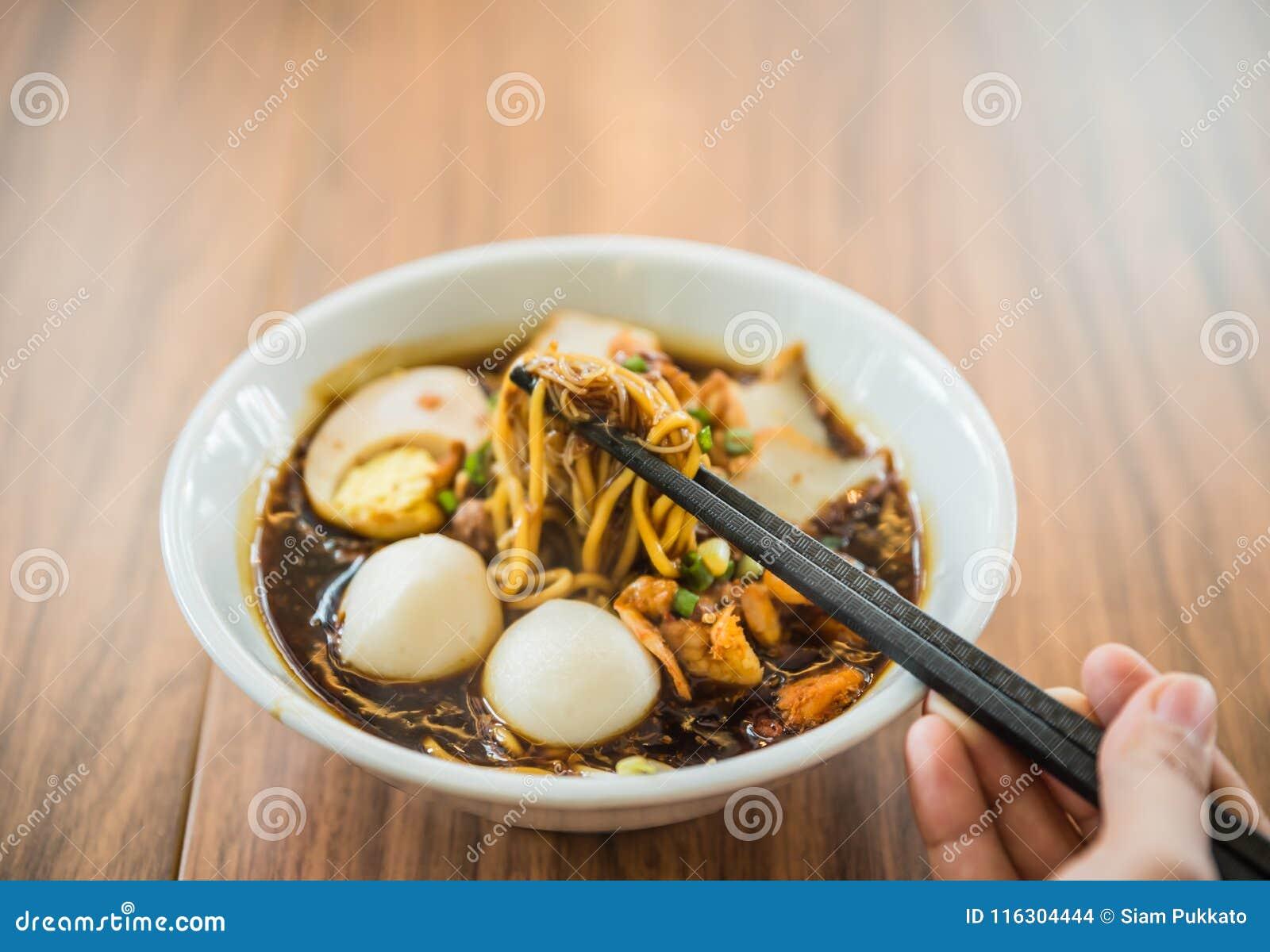 Miękka ostrości ręka z Chińskimi chopsticks je kluski