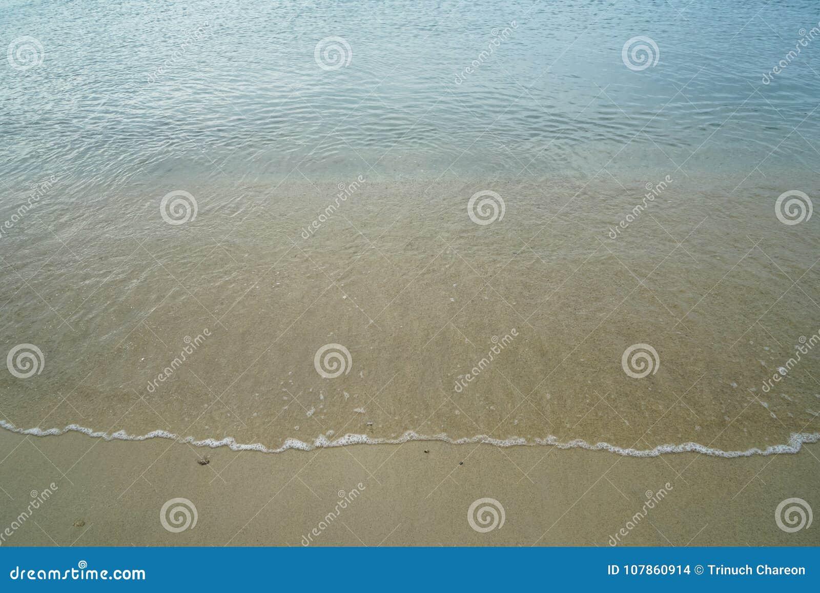 Miękka pastelowa czysta piaskowata plaża z świeżą jasną wodą morską i biała foamy fala wykładamy tło i copyspace na Ornos brzeg