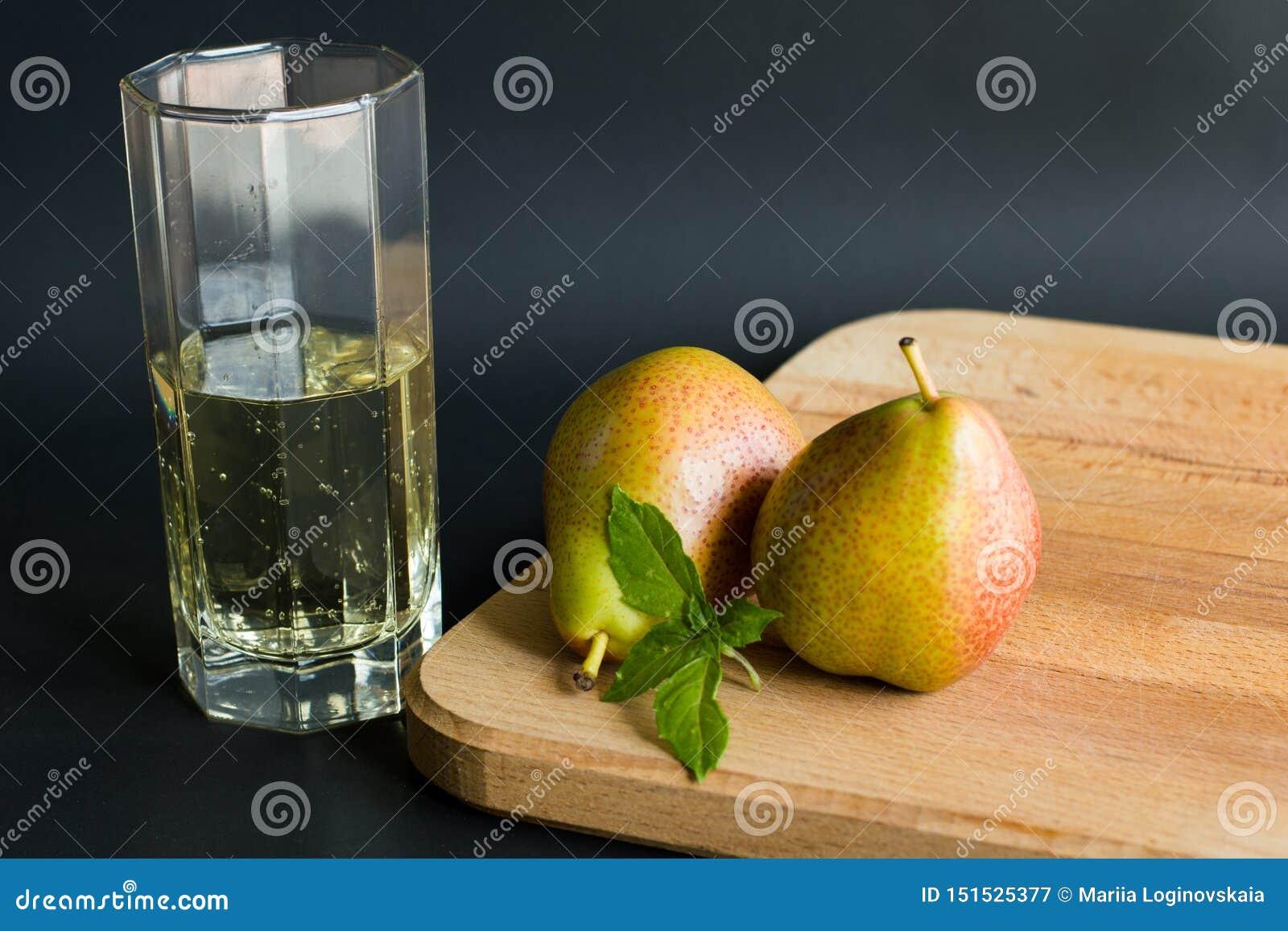Miękki bezalkoholowy bonkreta cydr w przejrzysty szklanym i dwa bonkretach z świeżym basilem opuszcza na drewnianej tnącej desce
