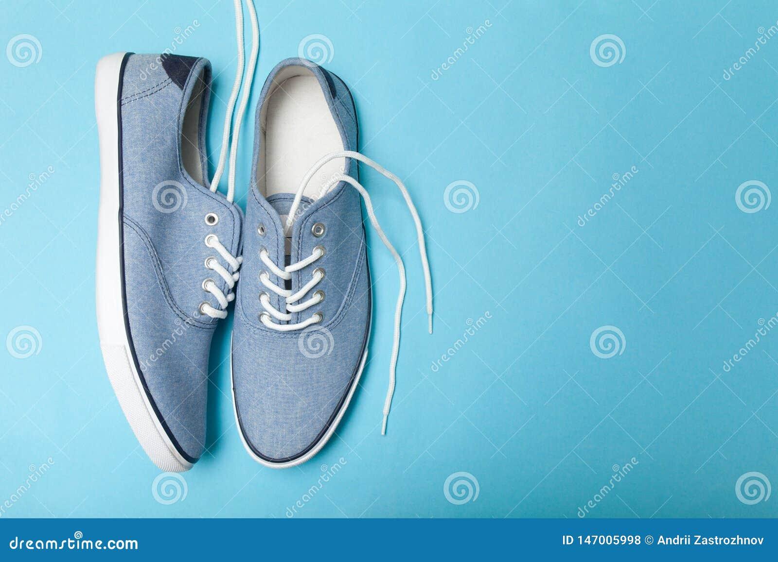 Miękkiego lata wygodni błękitni sneakers na błękitnym tle Odbitkowa przestrze? dla teksta