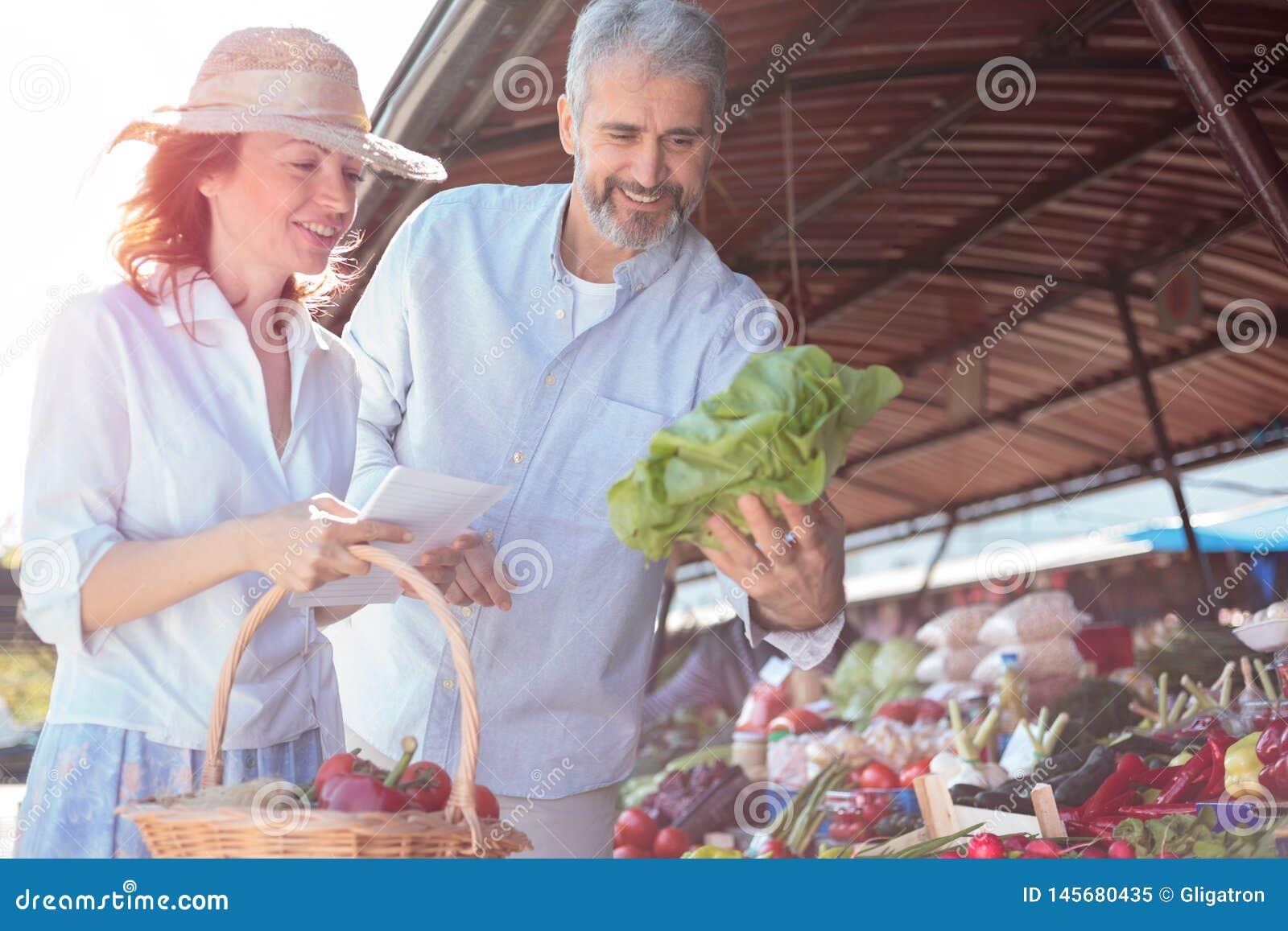 Mi couples adultes heureux achetant les légumes organiques frais dans un marché