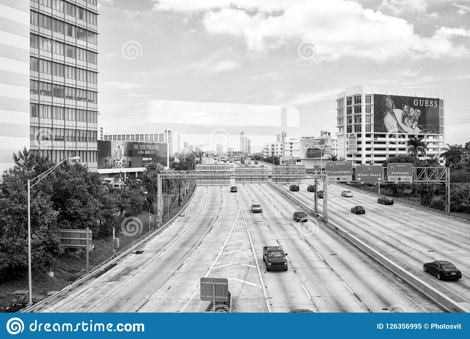Highway or roadway with cars and skyscrapers on cloudy blue sky. Road with traffic signs for transport vehicles
