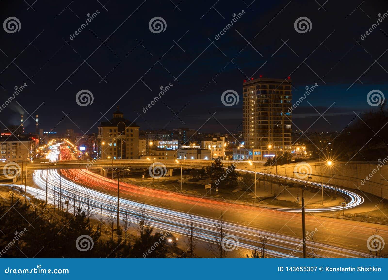 Miasto jedzie na drodze zaświeca i samochody Nowożytni budynki w nocy światłach