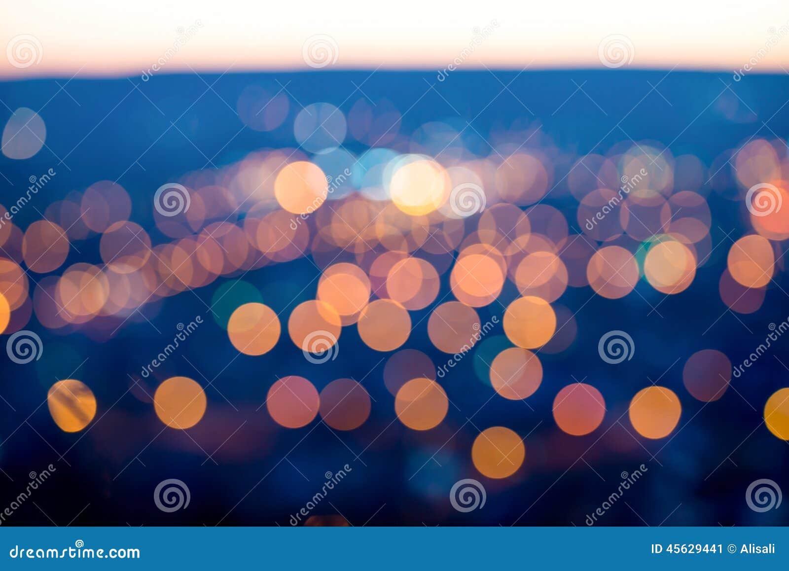 Miasto zaświeca w mrocznym wieczór z zamazywać tło, cl
