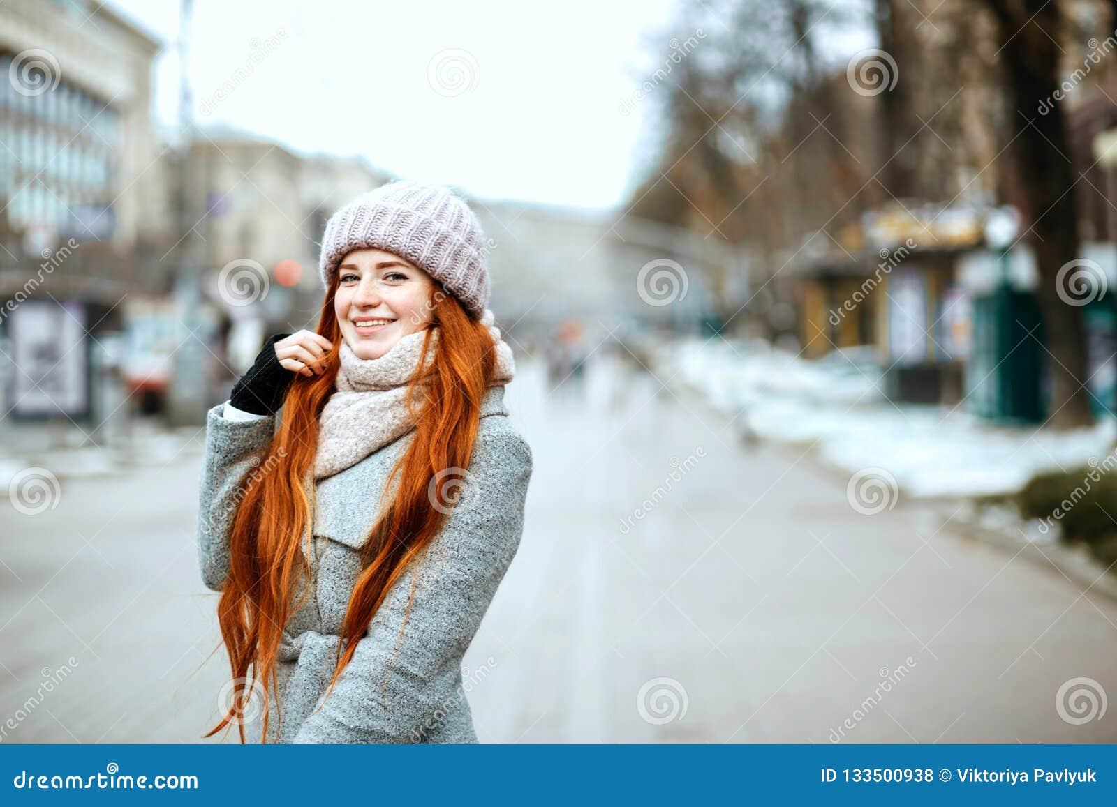 Miastowy portret pozytywny imbiru model z długie włosy jest ubranym w