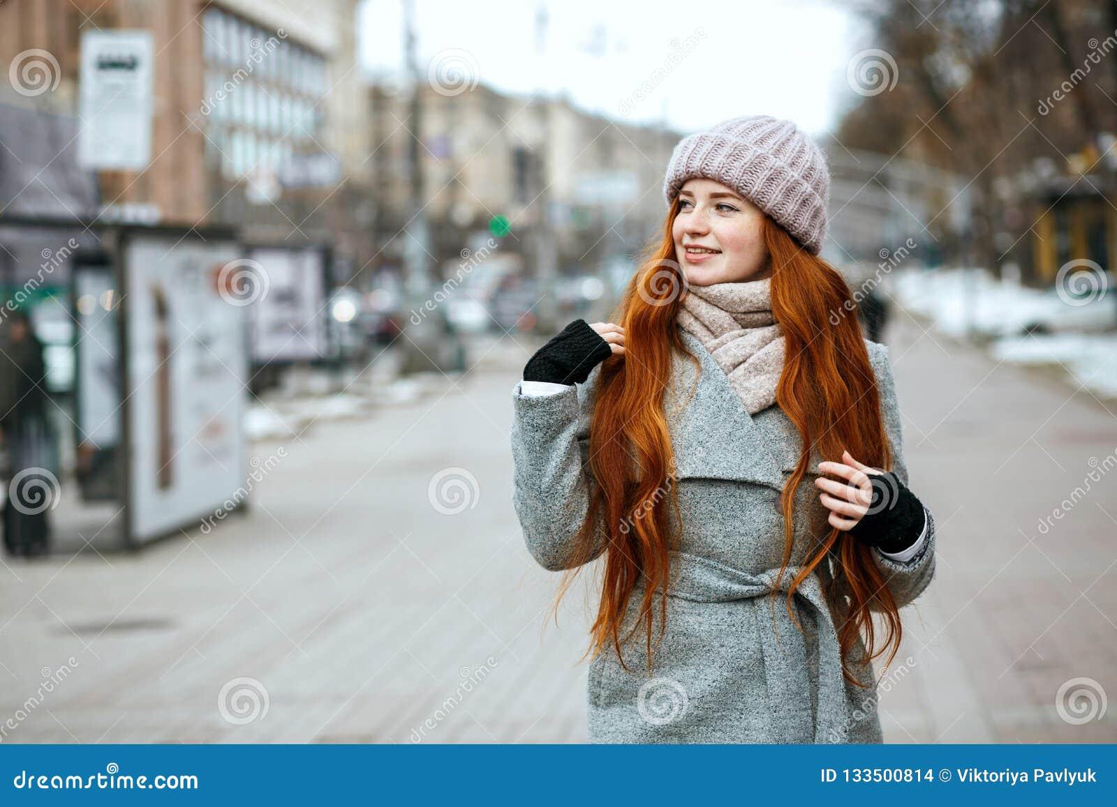 Miastowy portret prześwietna rudzielec dziewczyna z długie włosy jest ubranym w