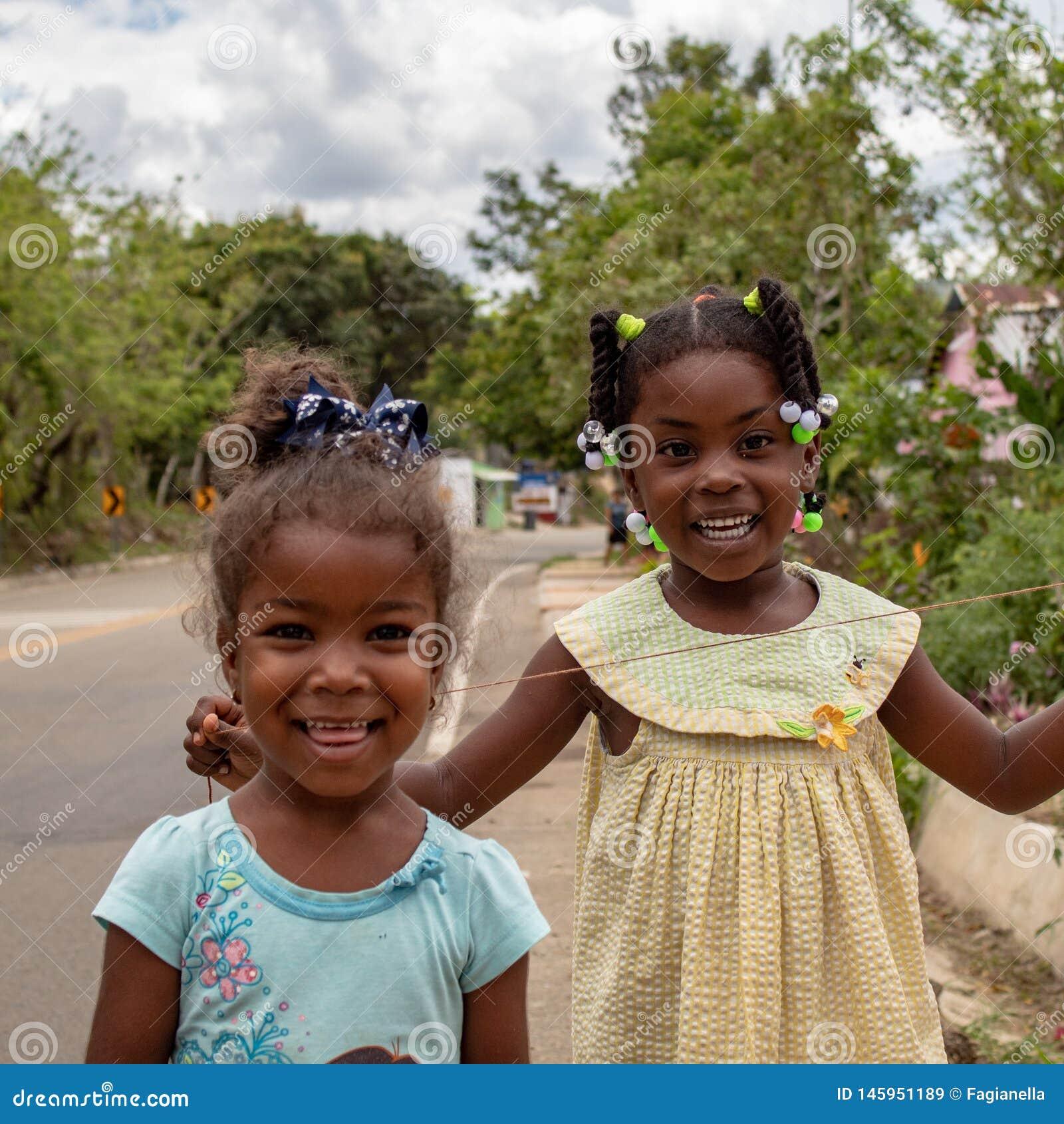 Miches, República Dominicana, o 16 de abril de 2019/duas meninas coloridas locais novas que jogam com baloons no lado da estrada