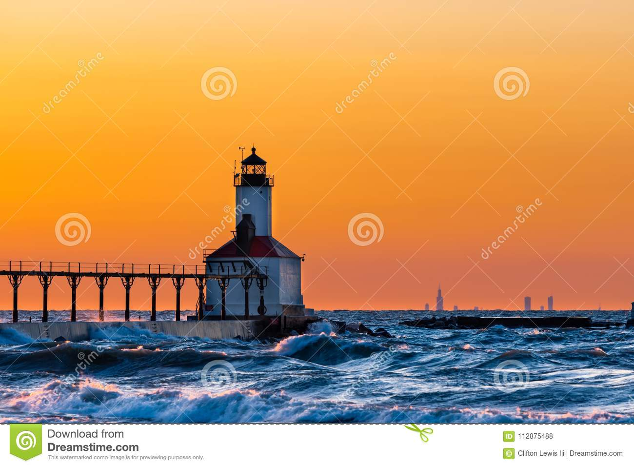 Michigan City, Indiana / USA : 03/23/2018 / Washington Park Lighthouse bathed in a beautiful sunset with Chicago looking over her