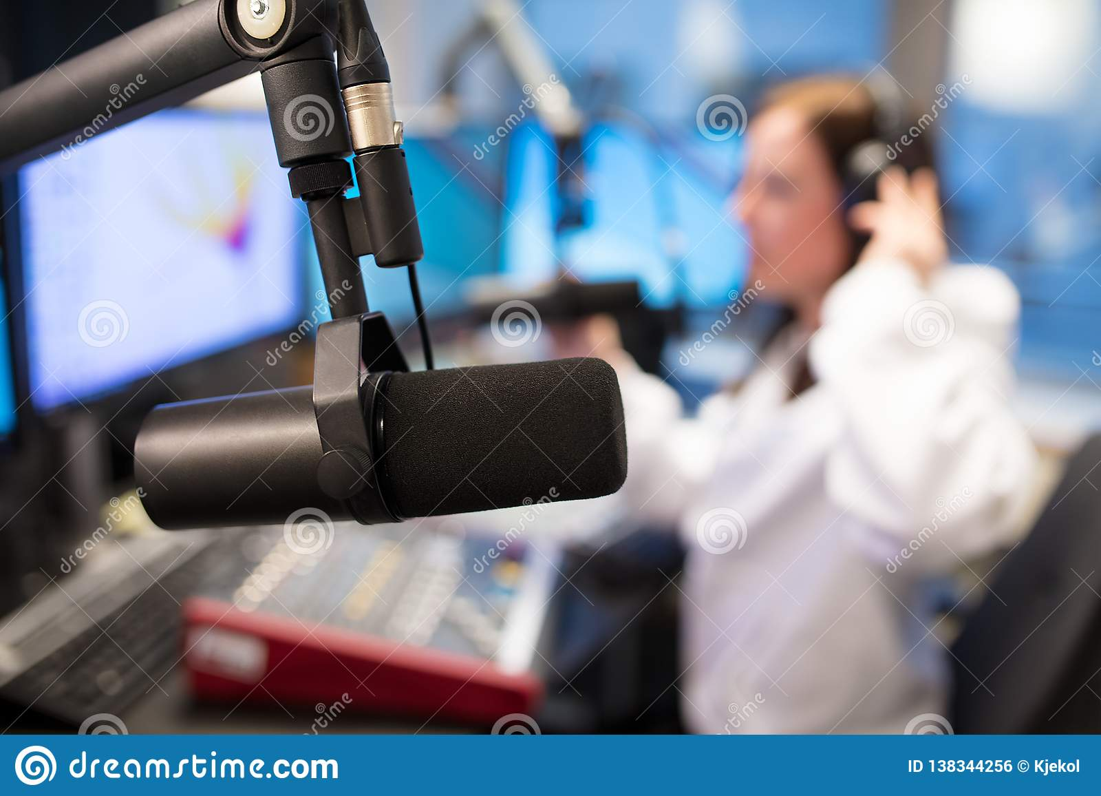 Micrófono del estudio en la estación de radio con el anfitrión femenino en fondo