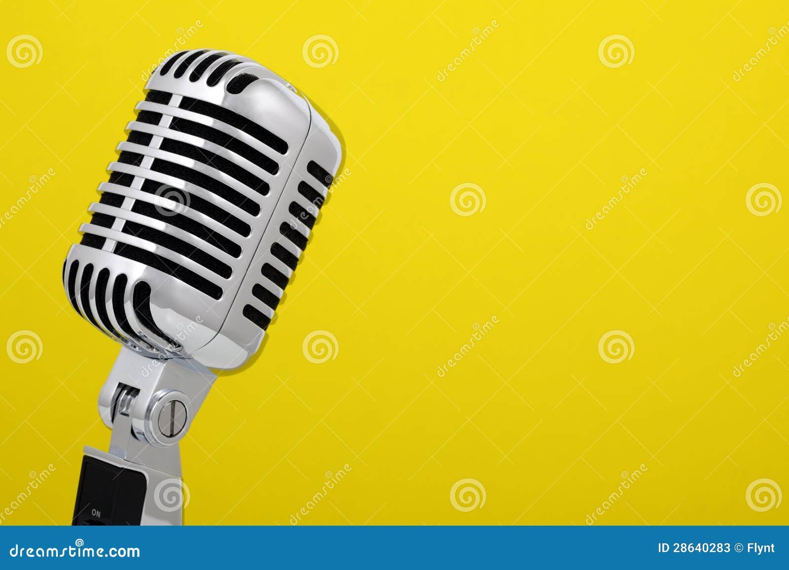 Micrófono del vintage aislado en amarillo