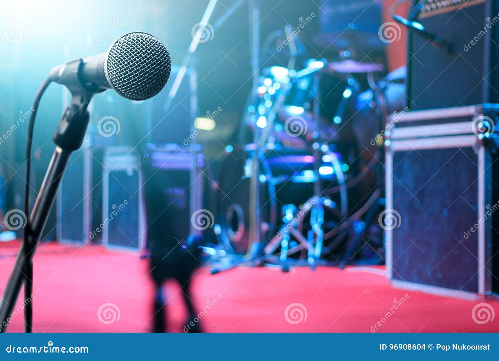 Micrófono e instrumento de música en fondo de etapa
