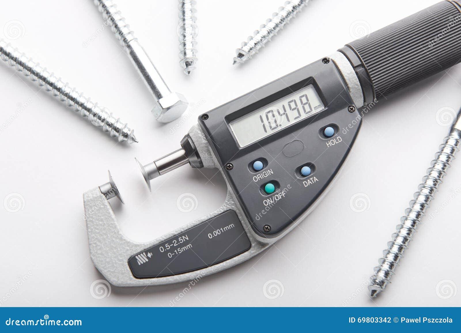 Micrômetro de Digitas com medida ajustável da pressão com os parafusos de aço no fundo branco