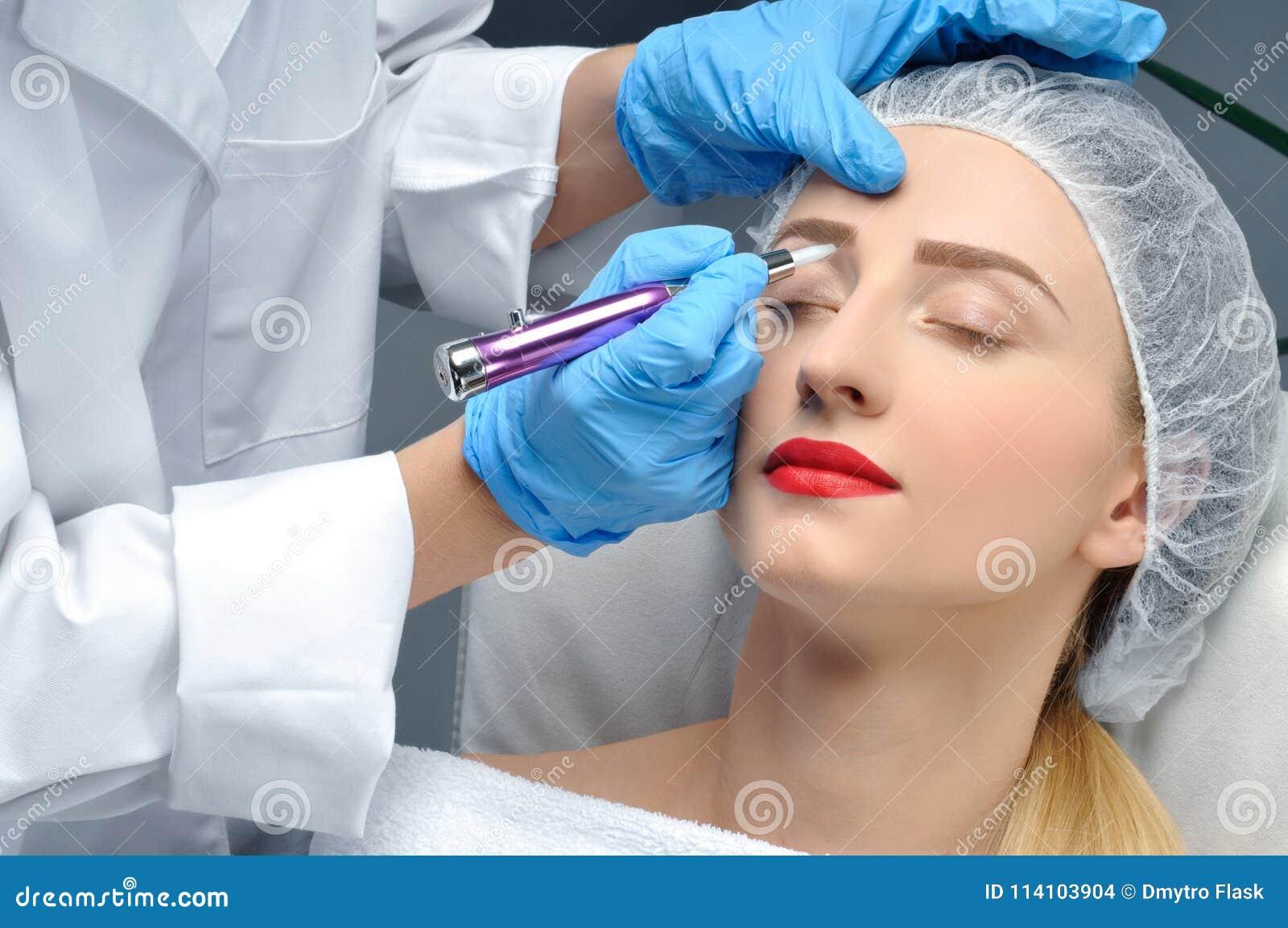 Microblading 做永久性的美容师构成 得到面部关心和纹身花刺眼眉的可爱的妇女