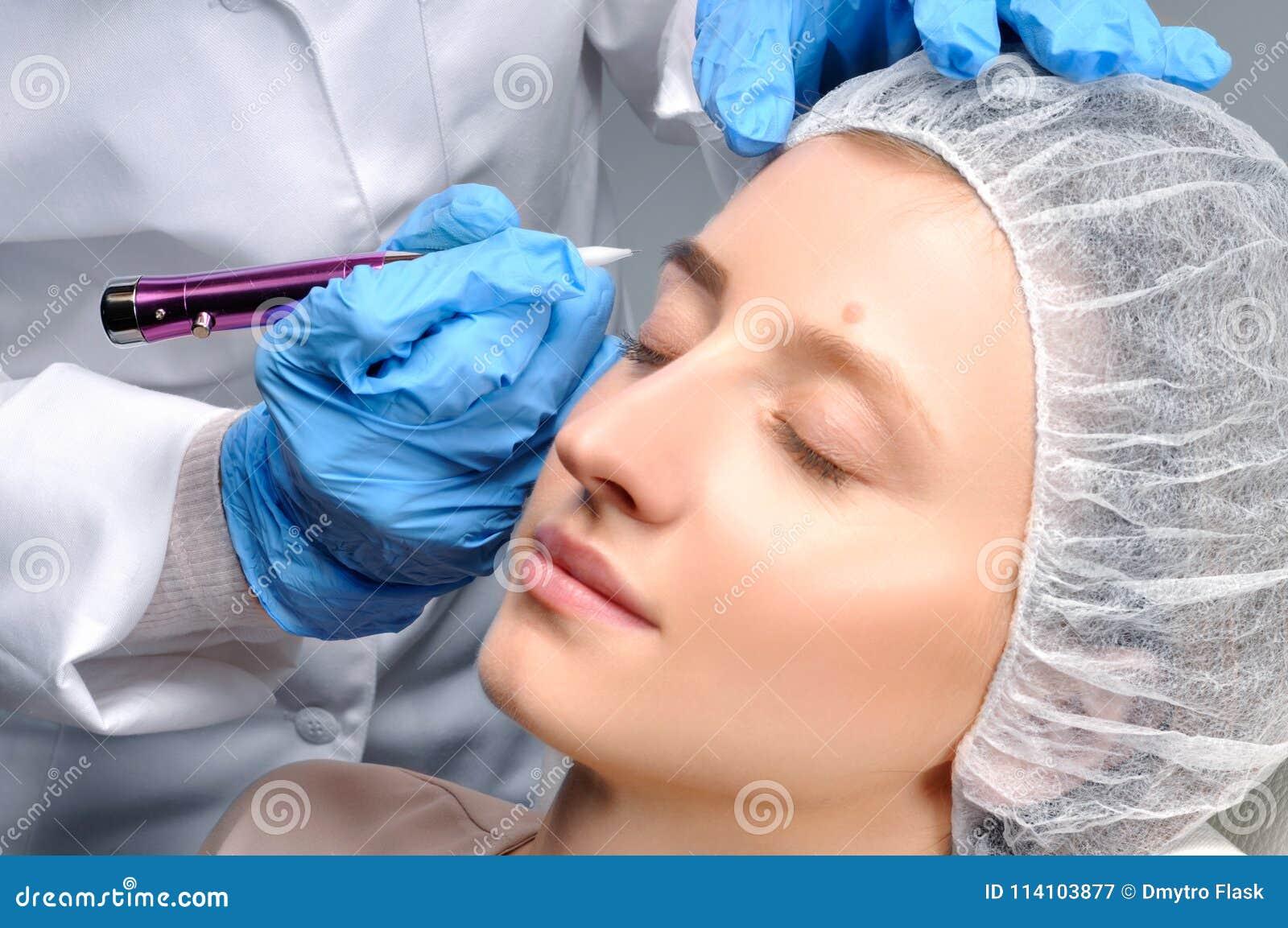 Microblading cosmetologist makeup που κάνει μόνιμο Ελκυστική γυναίκα που παίρνει τα του προσώπου φρύδια προσοχής και δερματοστιξι